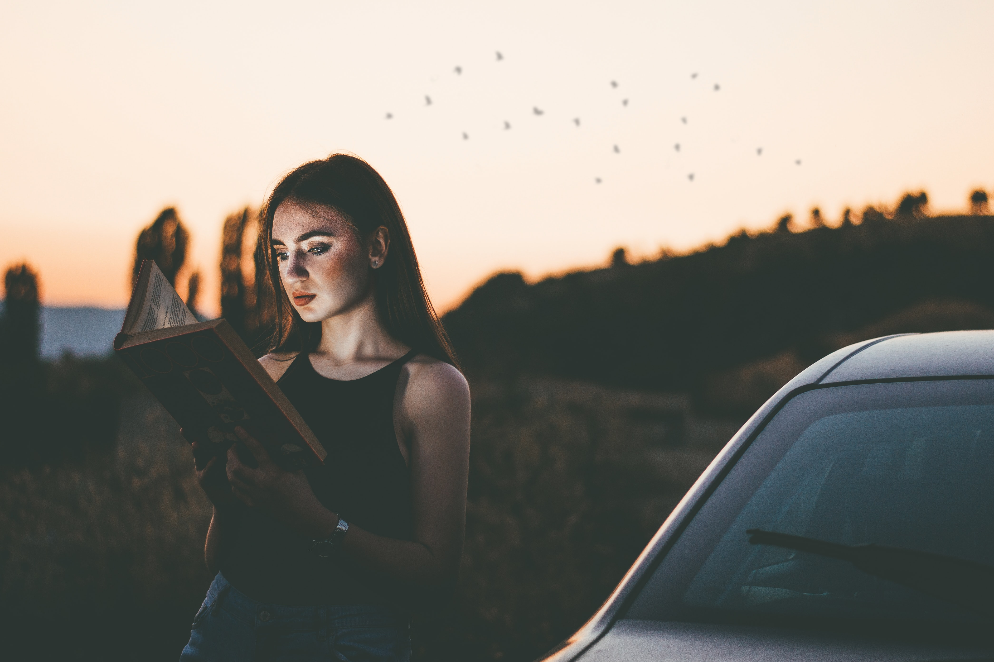 Young long hair woman reading a book by the car on a sunset in the nature