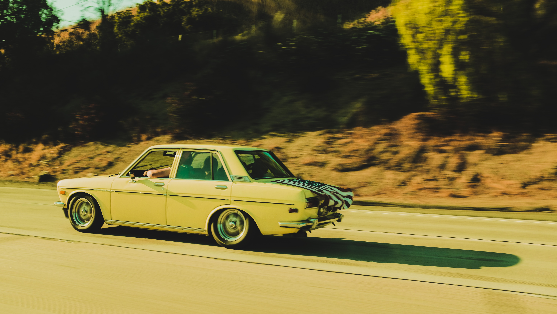beige sedan traveling near road during daytime