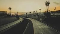 two gray concrete roads under gray truss bridge during sunset