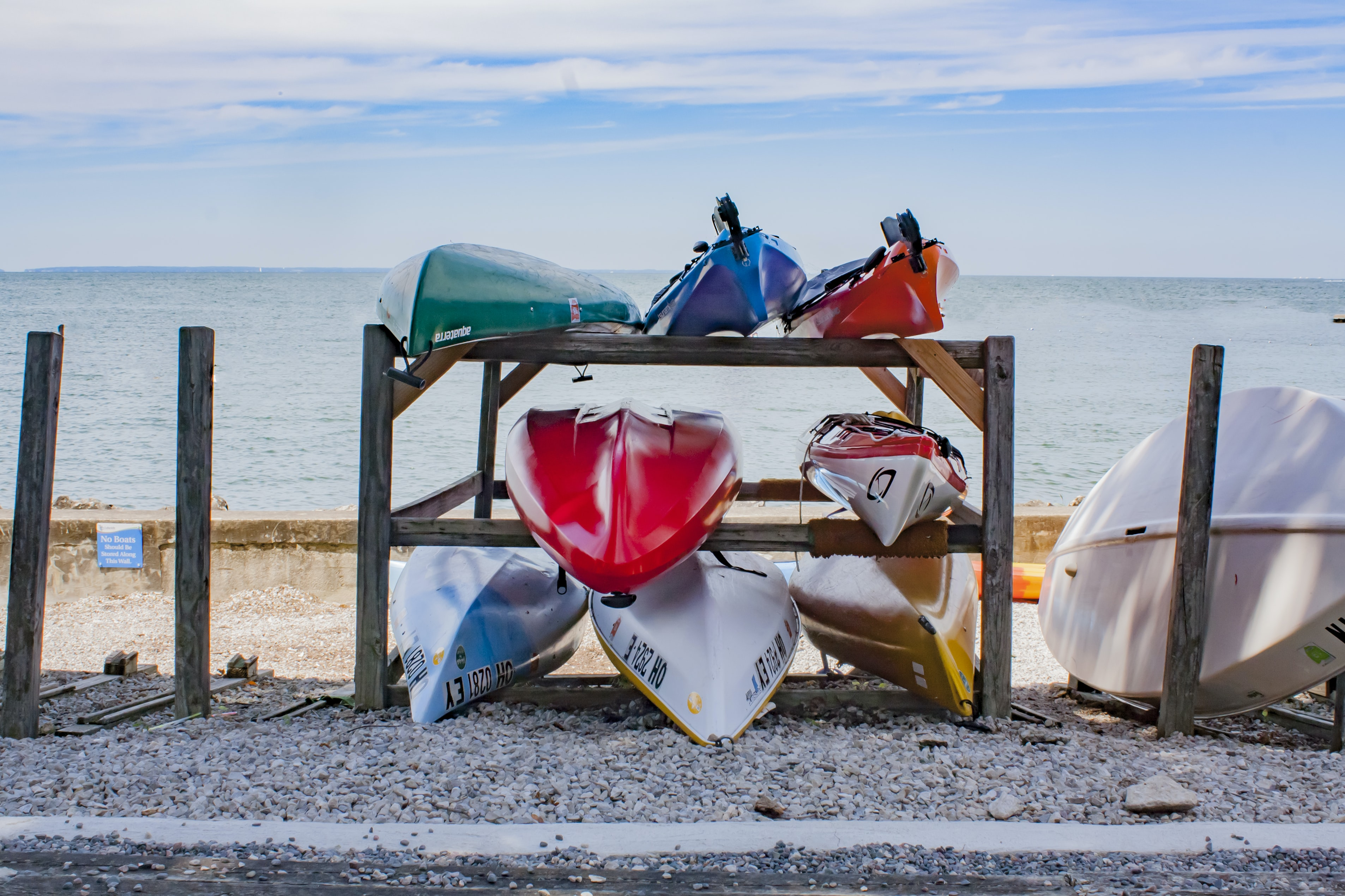 canoes on rack near body of water