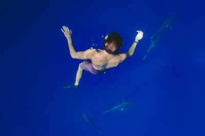 man freediving with fishes deep teams background