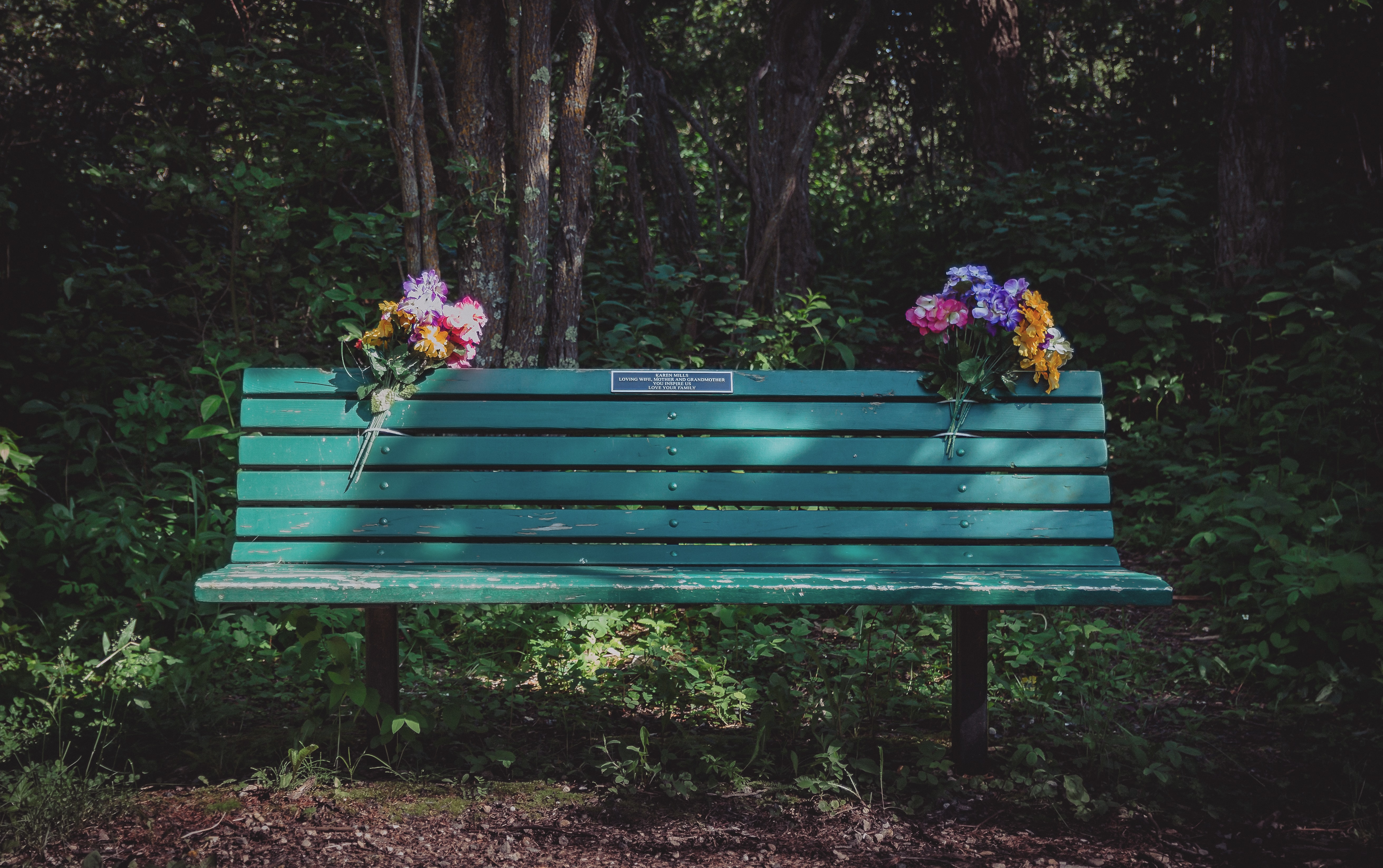 Two colorful flower bouquets attached to a green park bench with a plaque on it