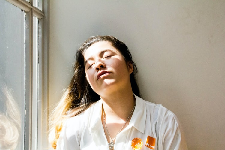 A photo of a woman leaning against a wall with her eyes closed beside a large window. She is bathed in sunlight.