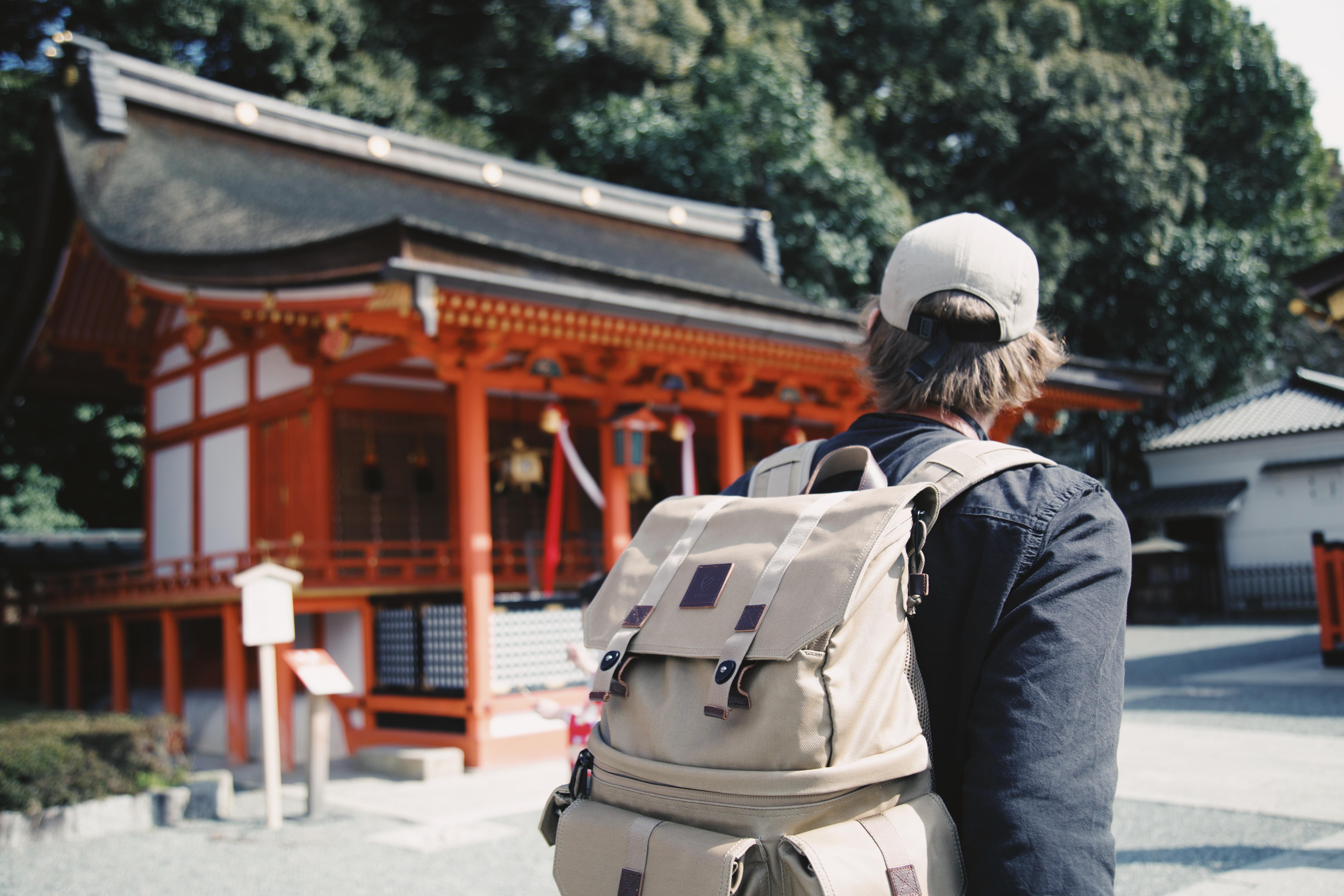 A person wearing a large backpack and baseball cap faces a building in Fushimi Inari Taisha