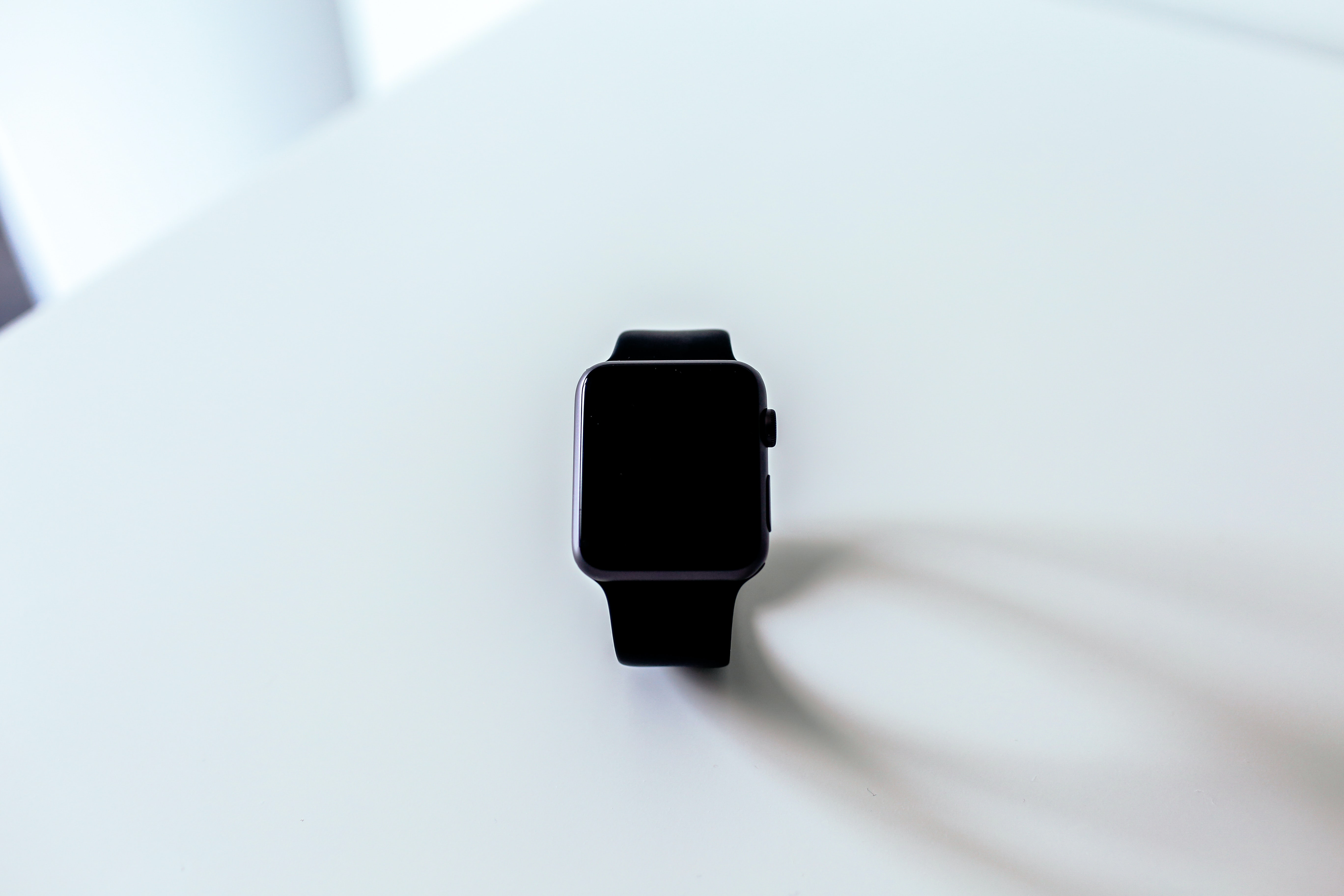 Apple wrist watch with a black screen sits on a white surface and casts a shadow