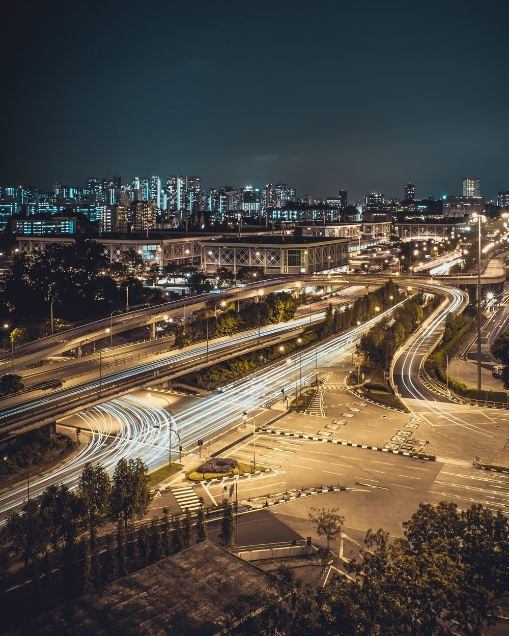aerial timelapse photography of cars passing on road intersection at night time