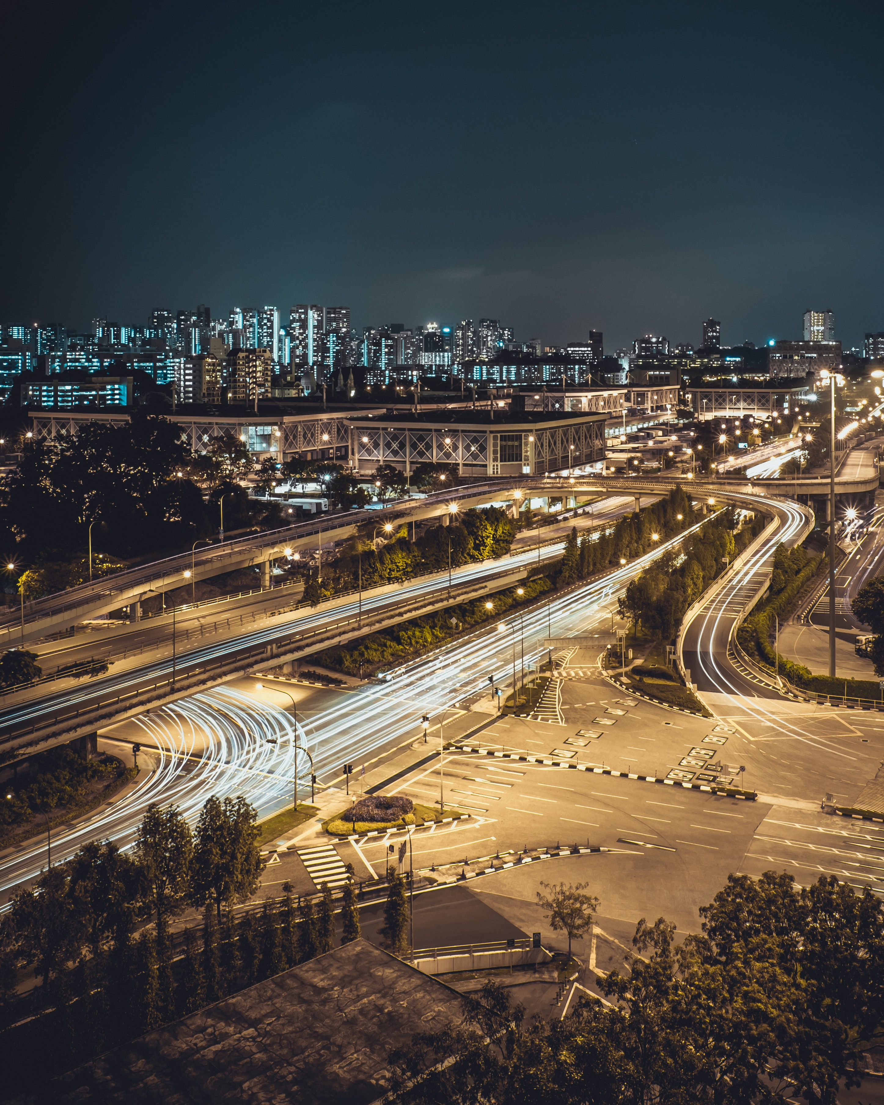 Bright light trails on streets leading to a large city