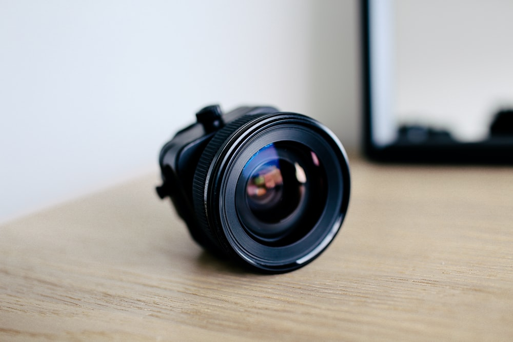 round black zoom lens on brown wooden surface