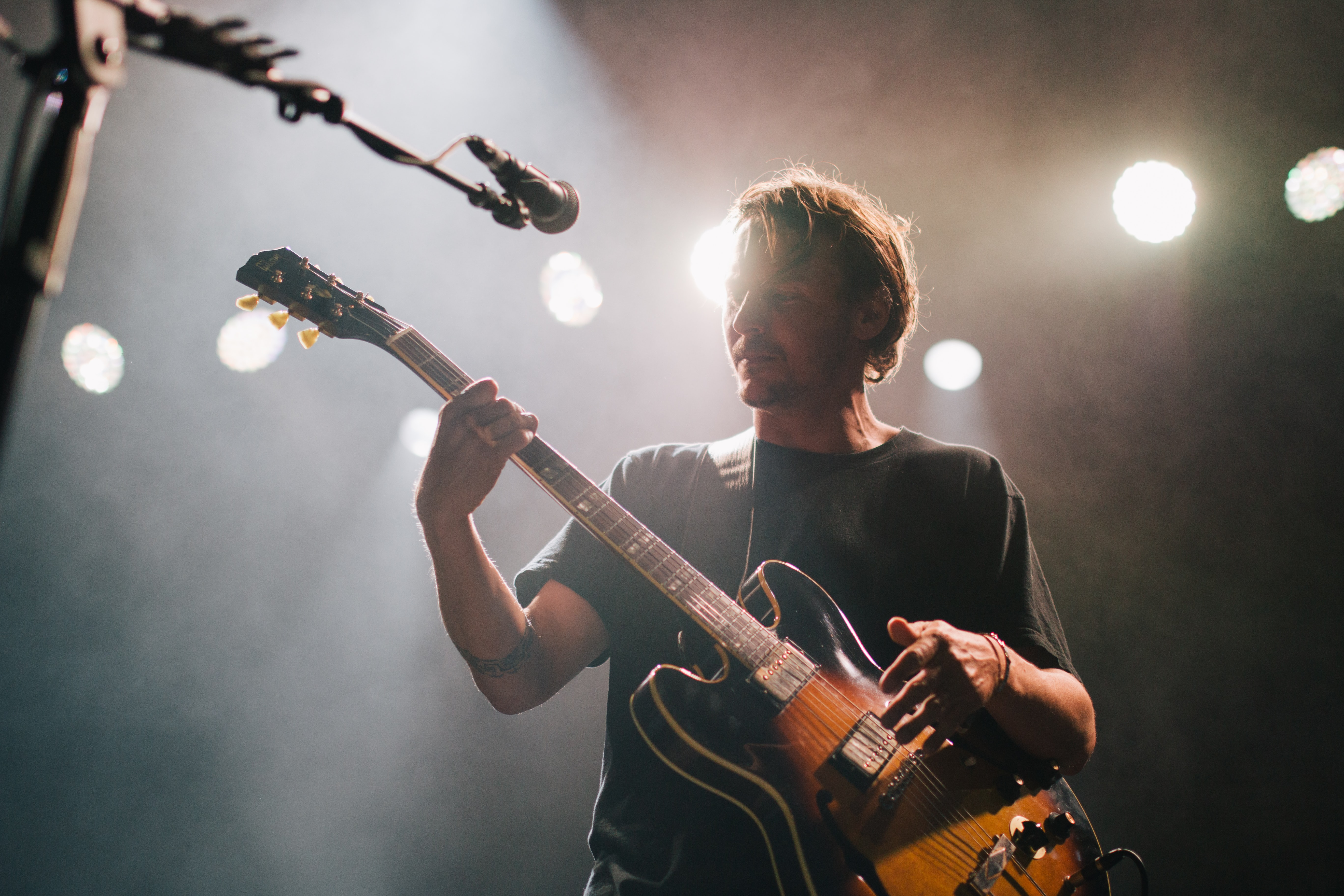 A guitar player thoughtfully strumming his electric guitar during a performance