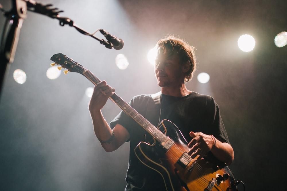 man playing guitar under spotlight