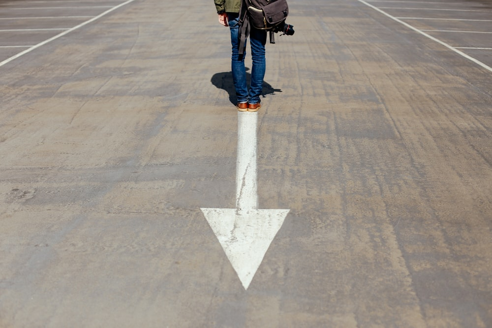 person standing on arrow sign on road