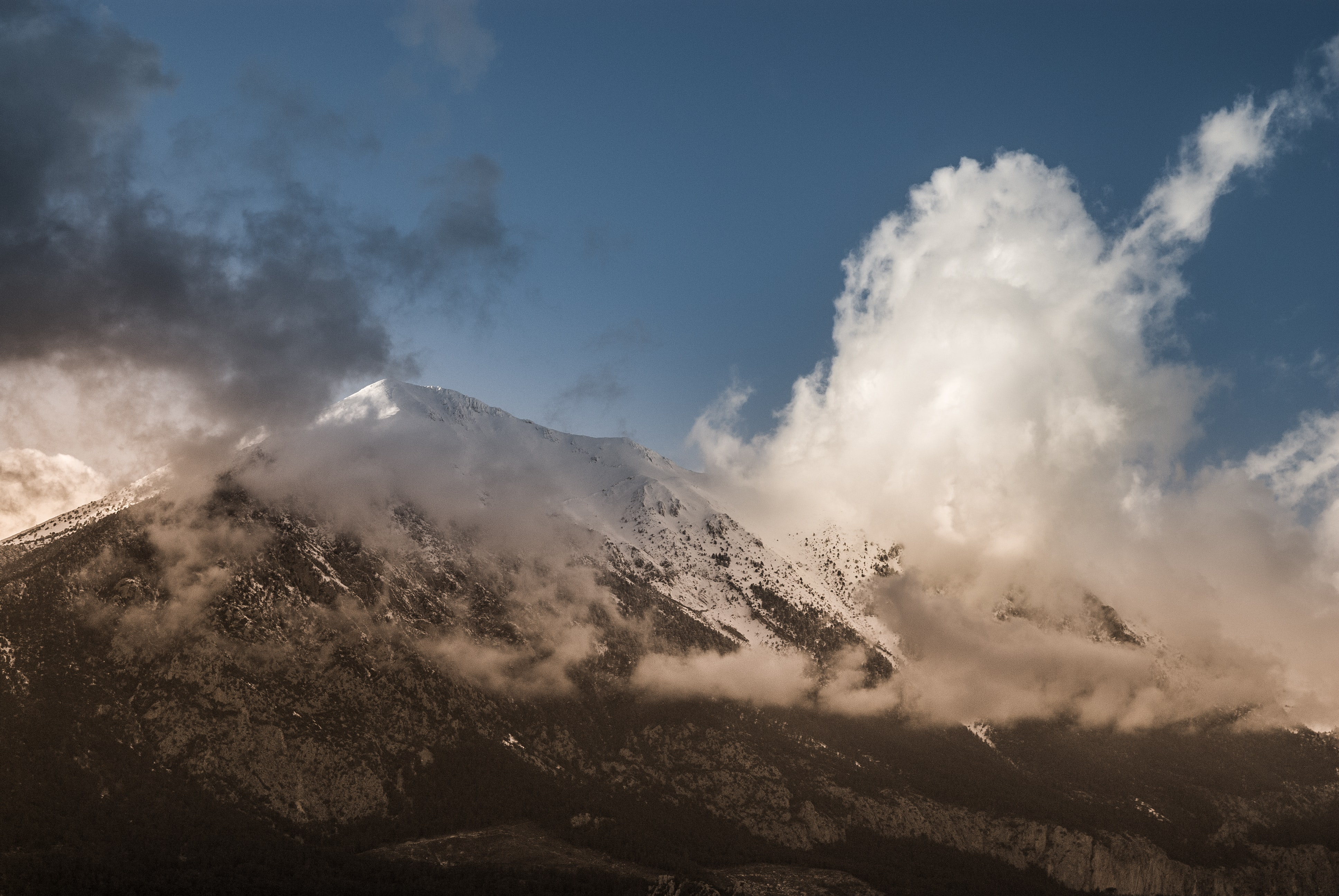 White clouds gathering around a snow-capped mountain