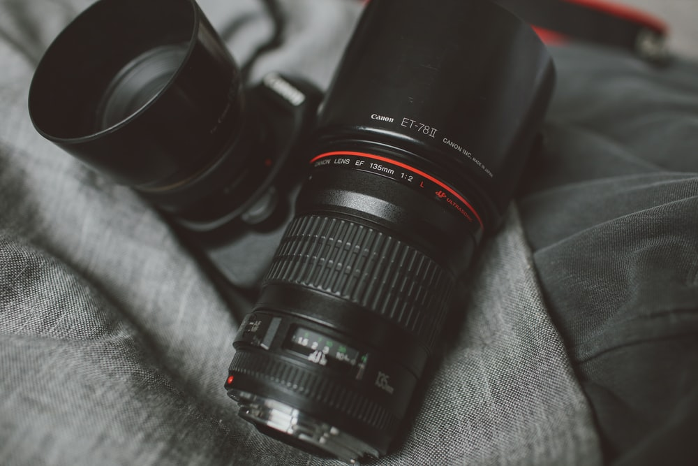 black DSLR camera and telephoto lens ongray pad