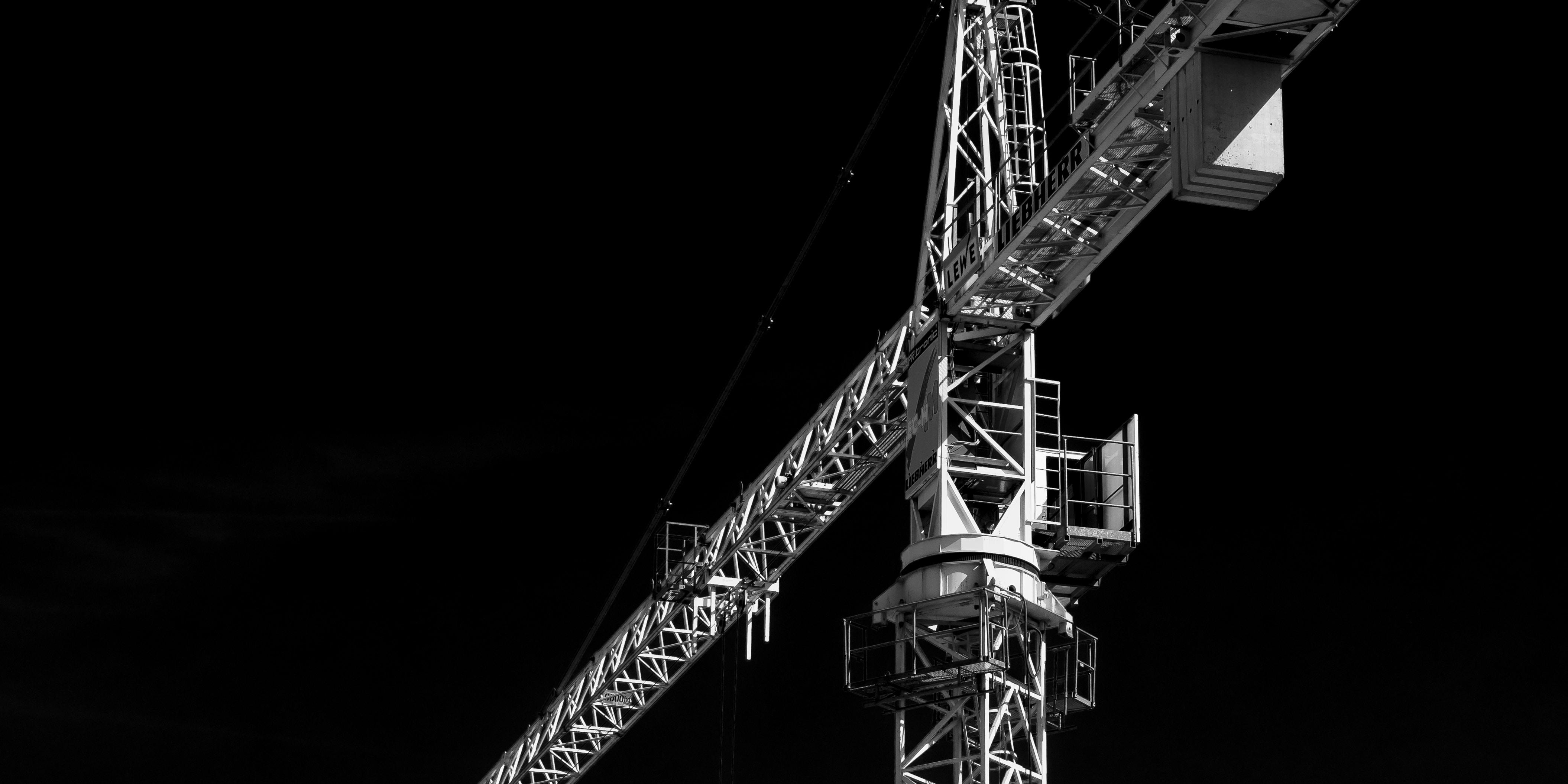 Construction site cranes form a T against a black sky