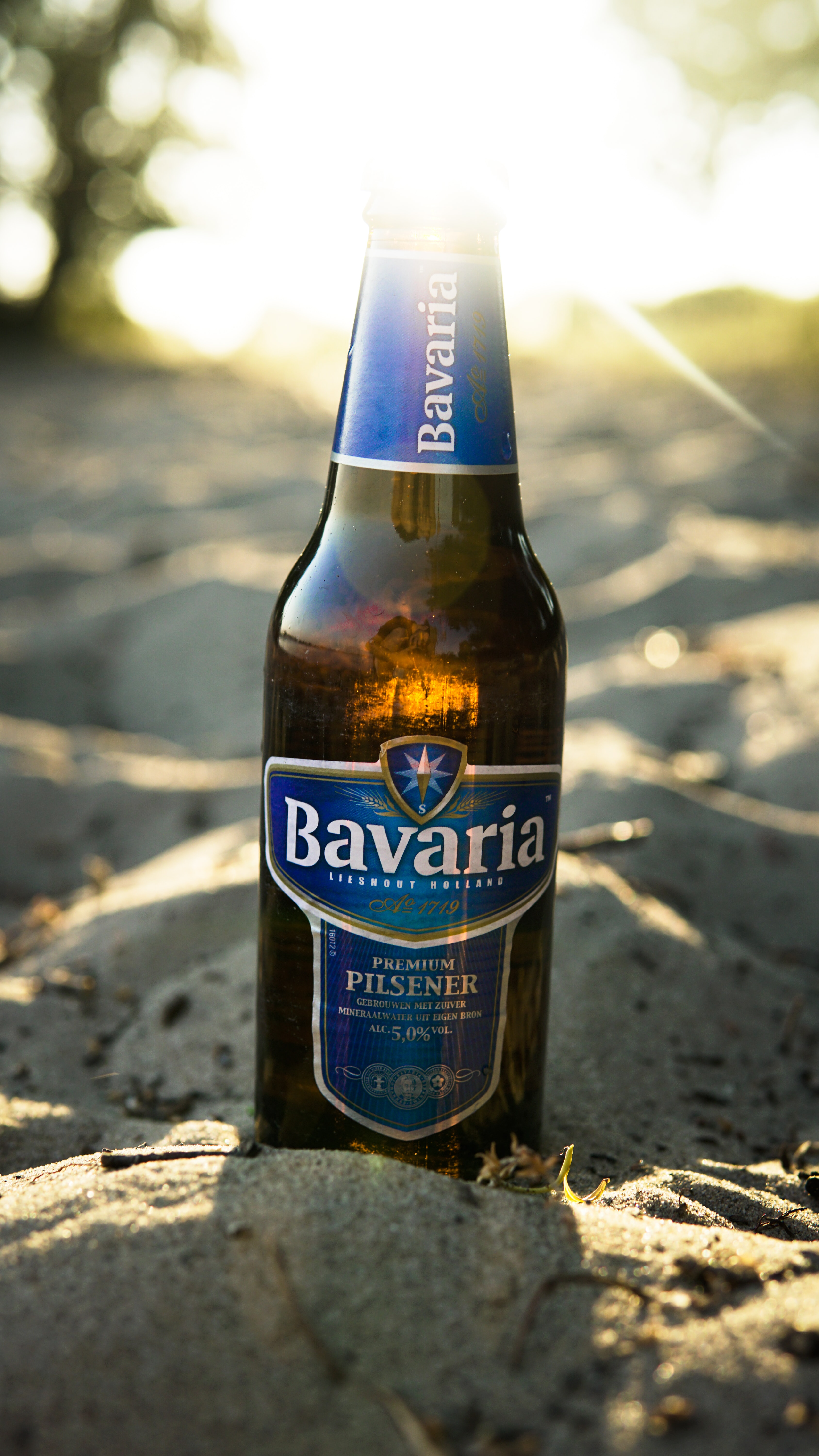 A macro view of a bavarian beer bottle on the sand in summer, Netherlands