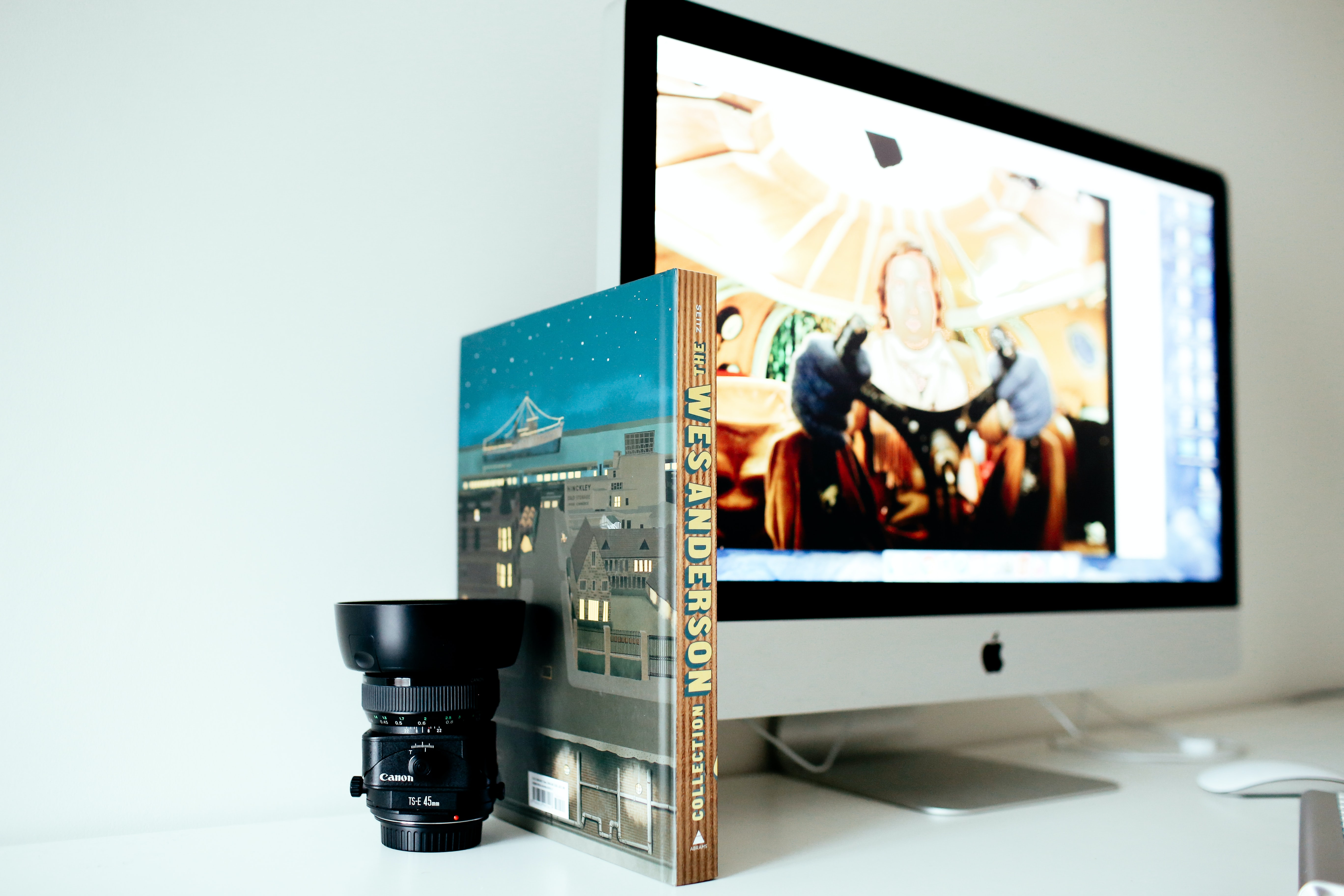 selective focus photography of black camera lens beside book and turned on iMac