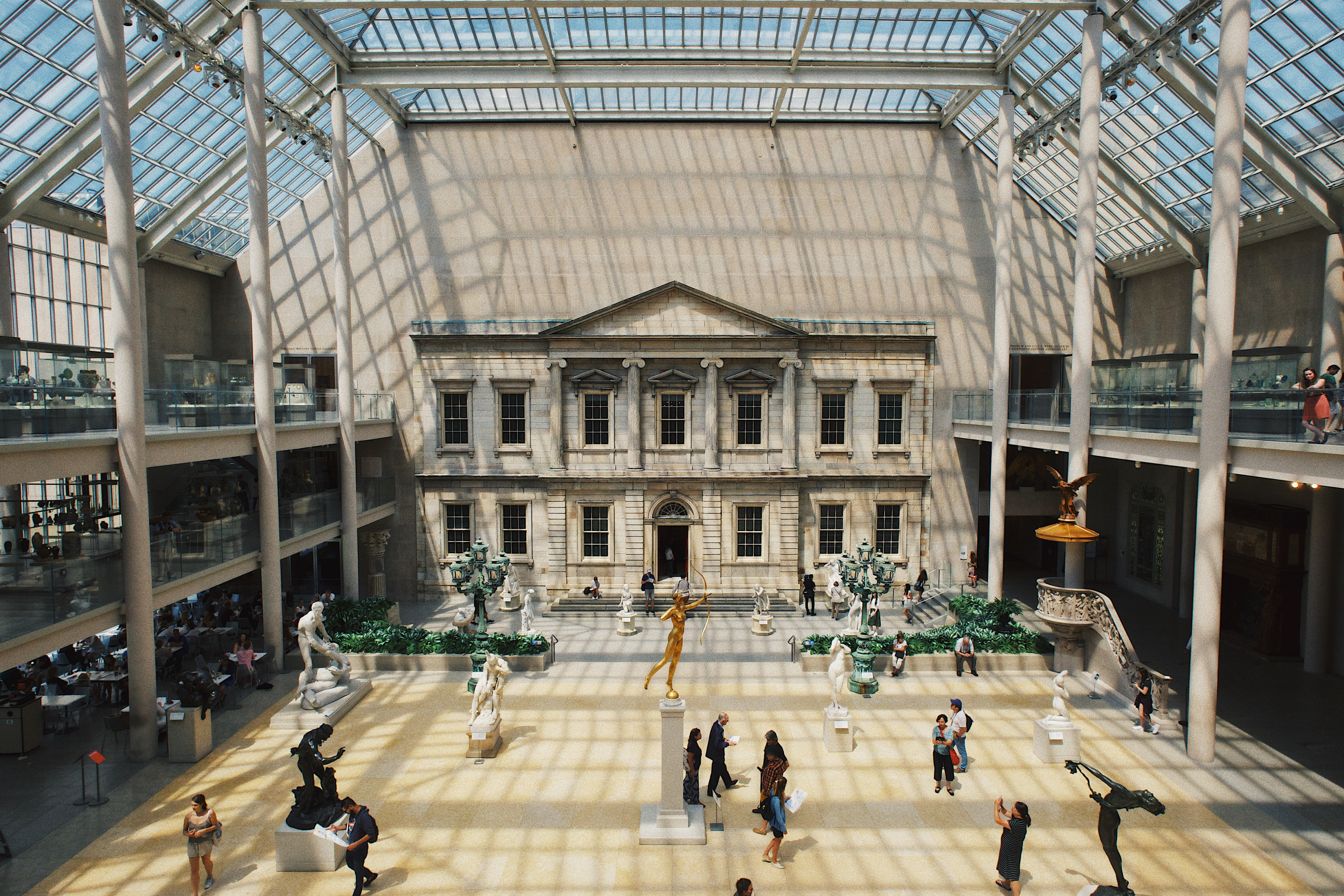 Museum interior in daytime with glass roof and people walking at The Metropolitan Museum of Art