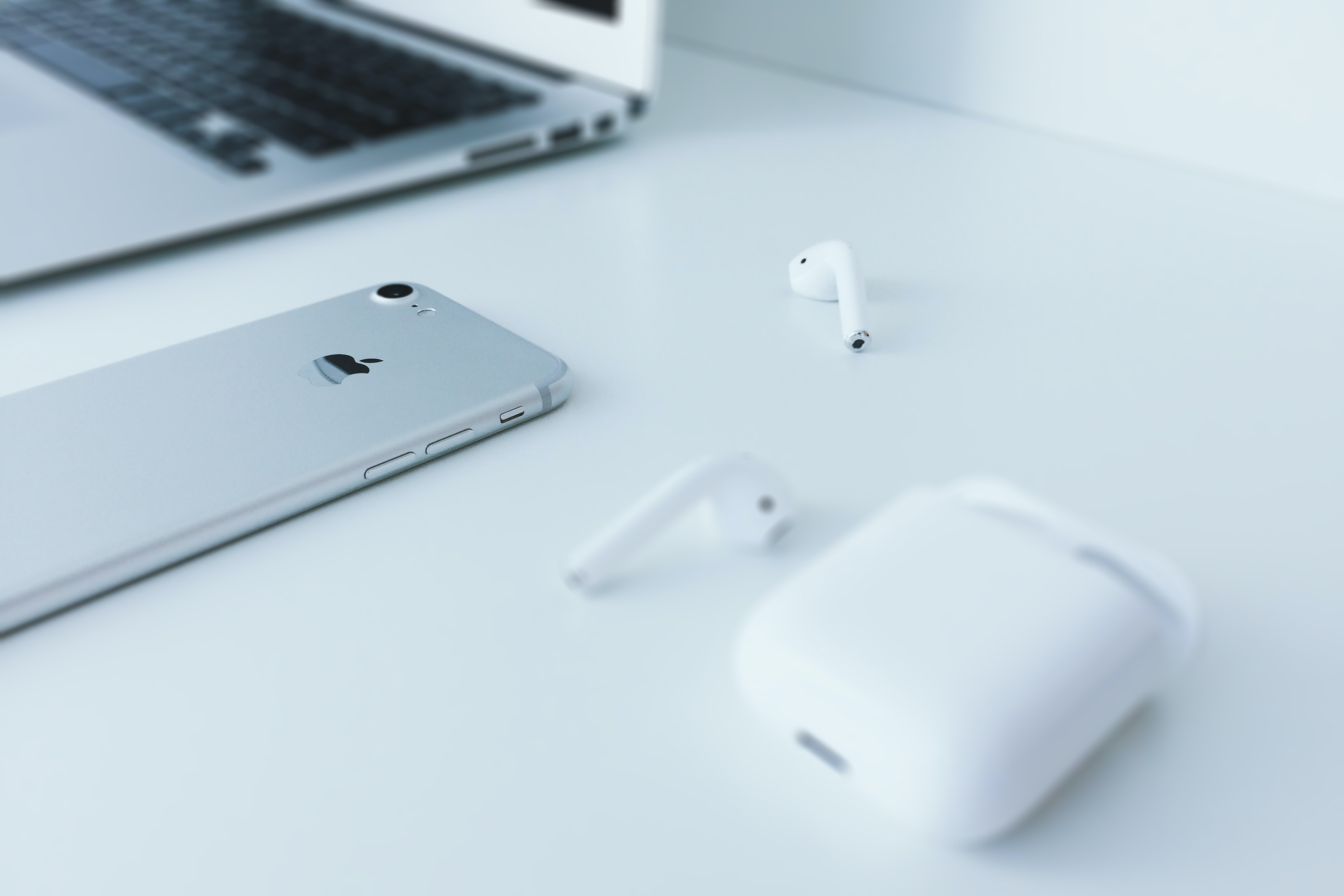 silver iPhone 7 lying on white surface near Apple AirPods