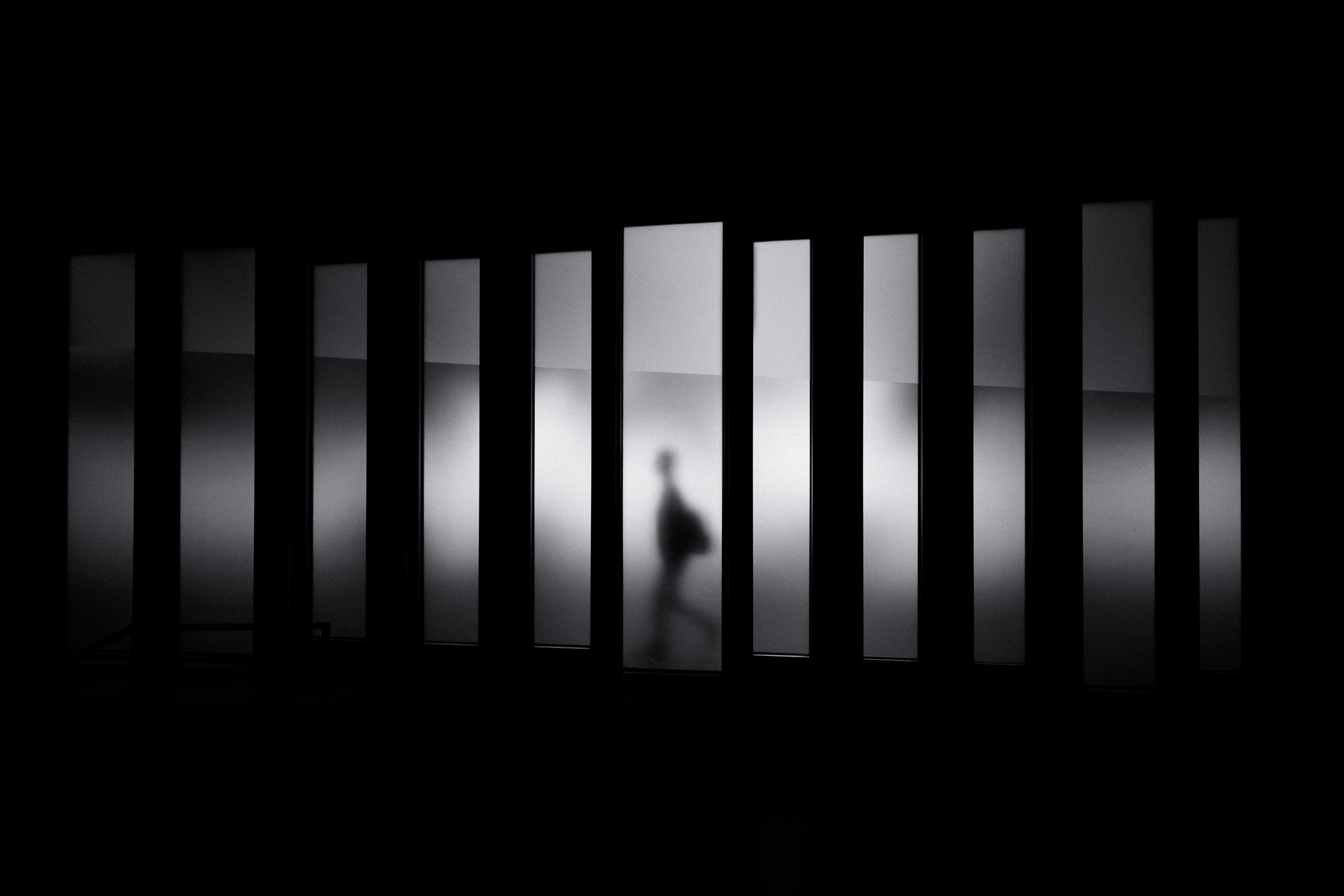 Black and white shot of person silhouette walking in hallway, Museu de Design de Barcelona