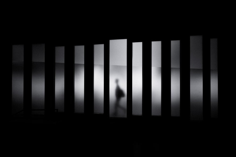 Download black wallpapers unsplash black and white shot of person silhouette walking in hallway museu de design de barcelona voltagebd Images