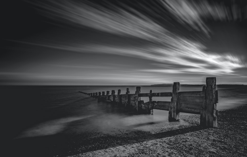 grayscale photo of wooden fence on sand