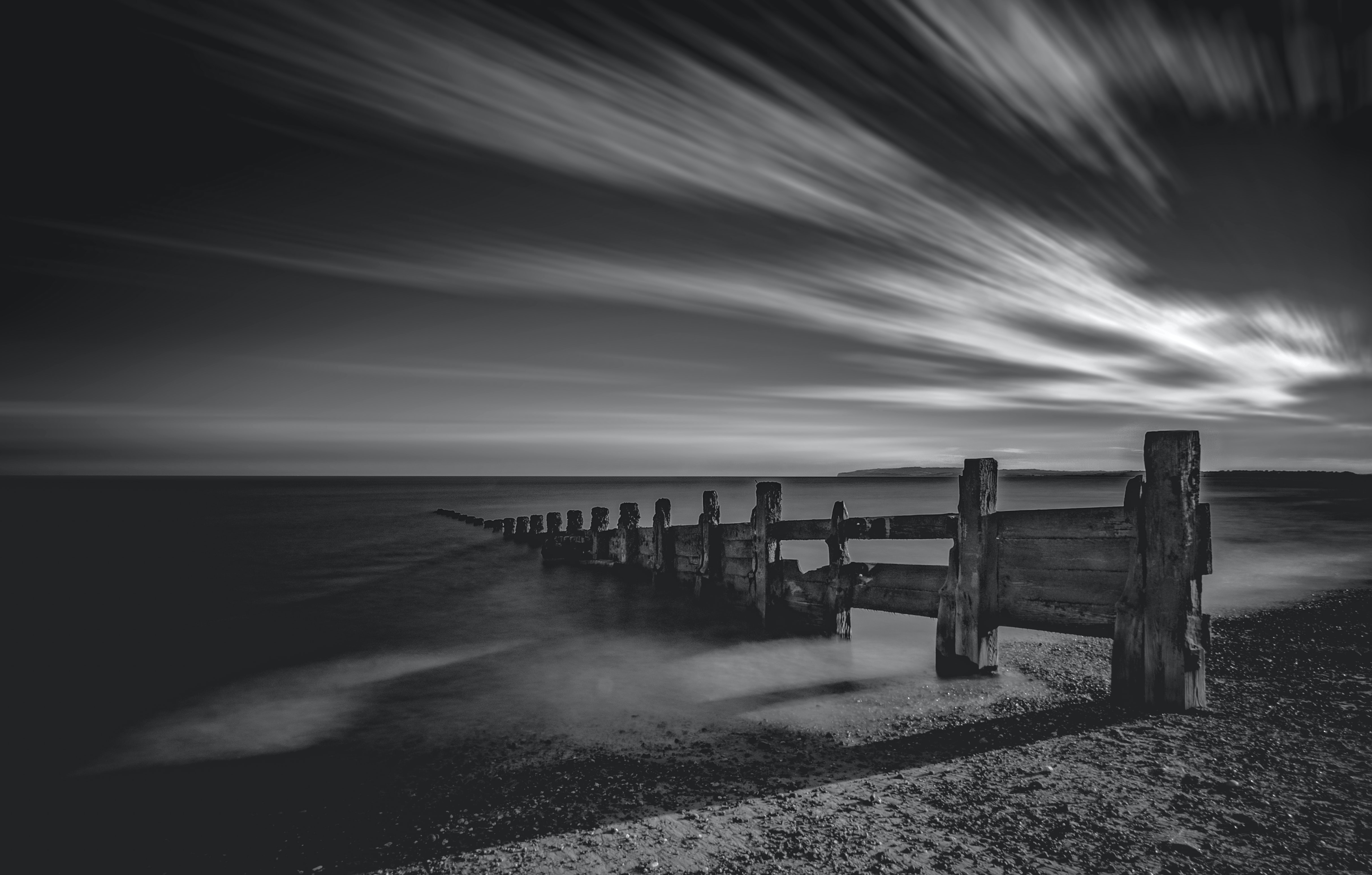 Black and white time-lapse photograph of wooden fence going into the ocean at Camber Sands Beach