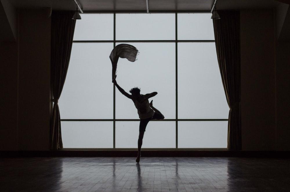 silhouette of man standing beside window photo – Free Dance