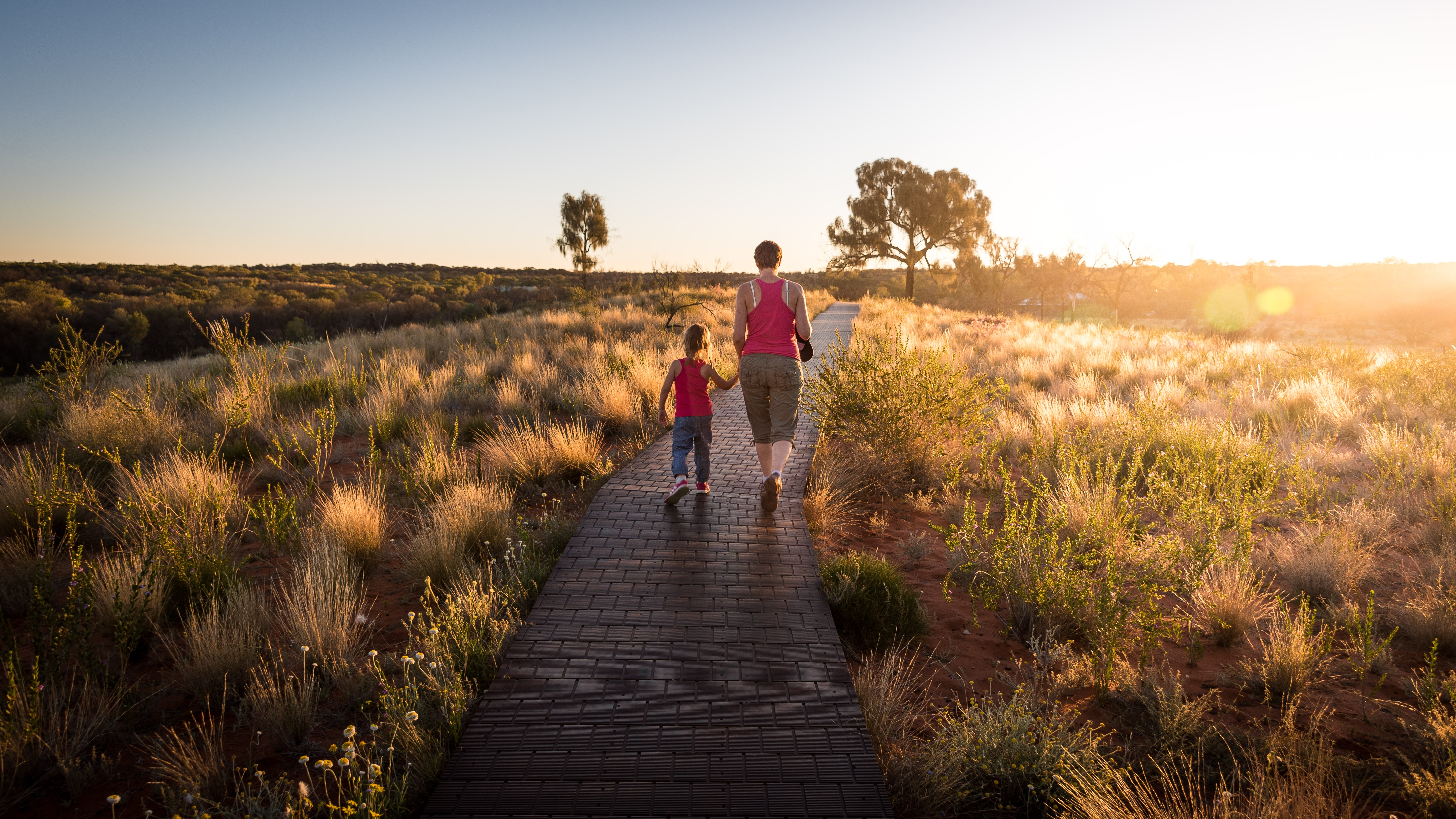 A mom and daughter both wearing pink vest tops, walking on a gangway surrounded by grass and foliage in the sunshine