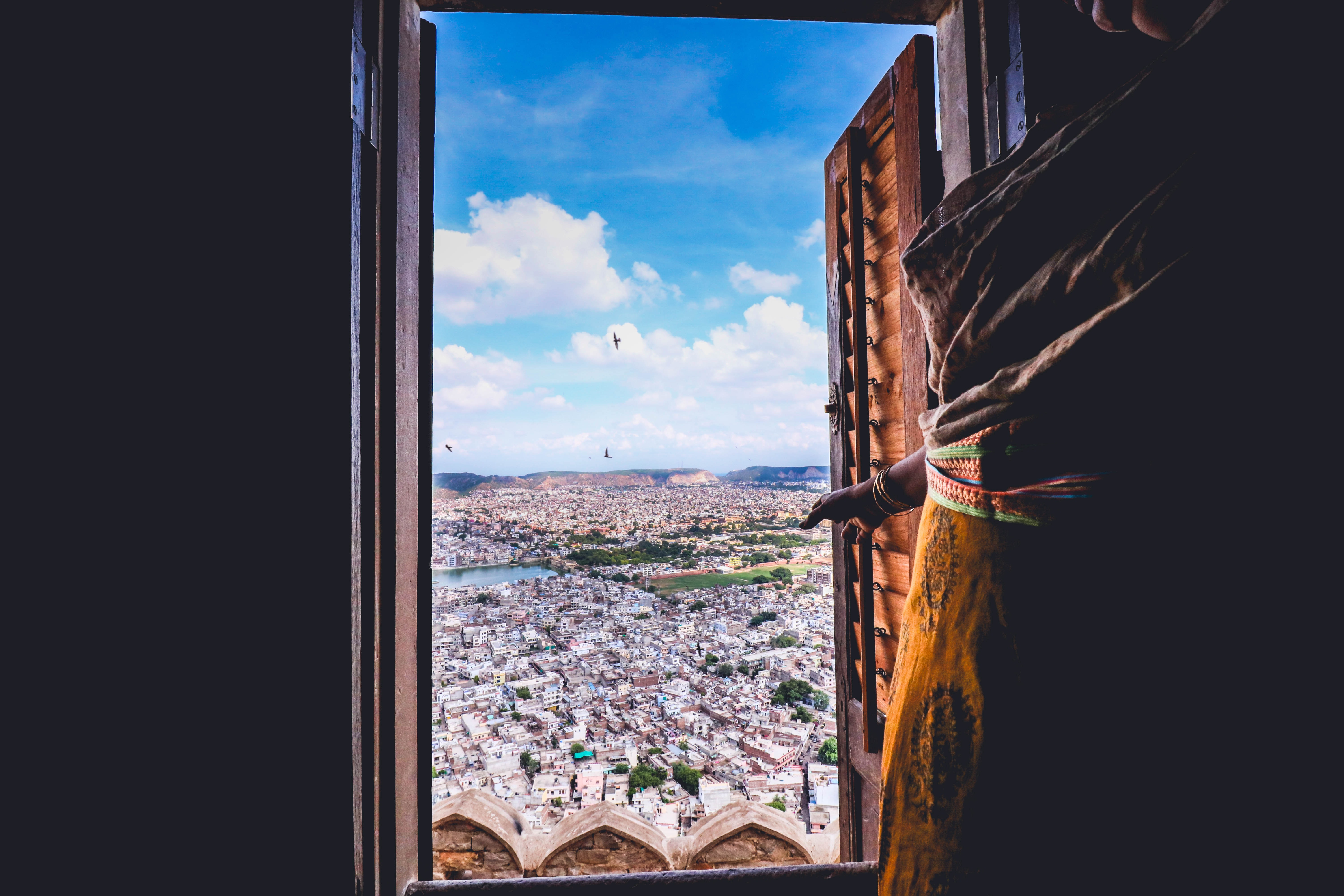 View of city from window with brown wooden shutter and cloudy blue sky, Nahargarh Fort