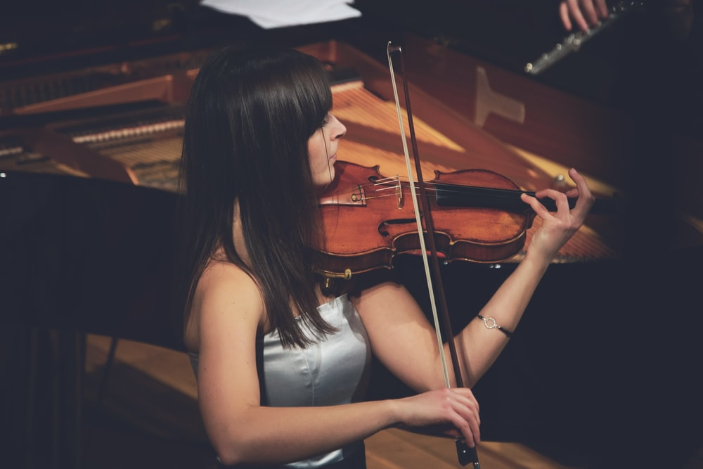 グランドピアノの横でバイオリンを弾く女性