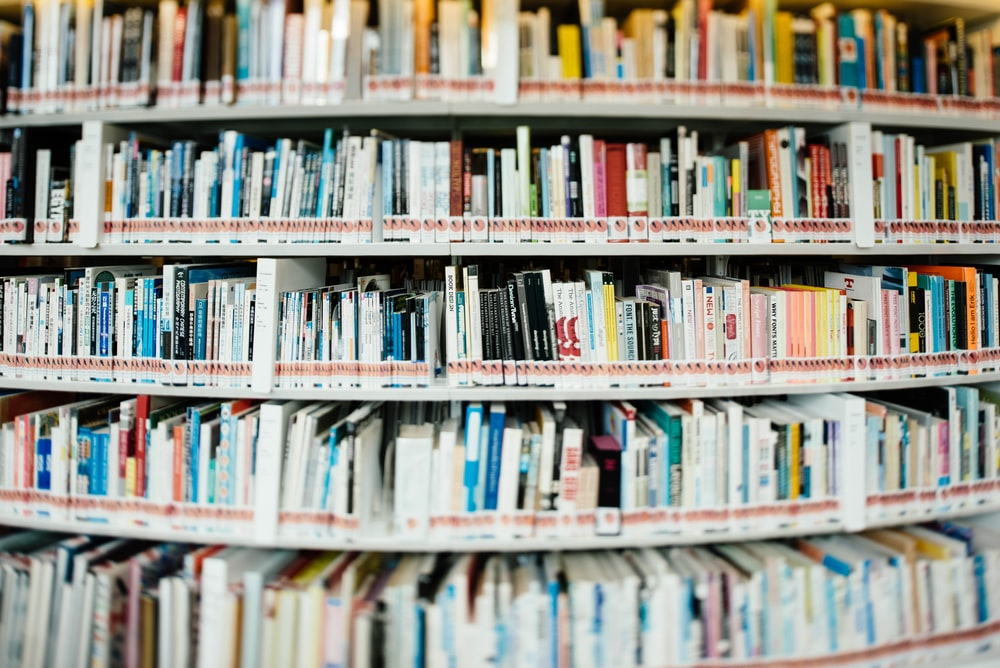 Stack Of Books On Bookshelf Inside Library