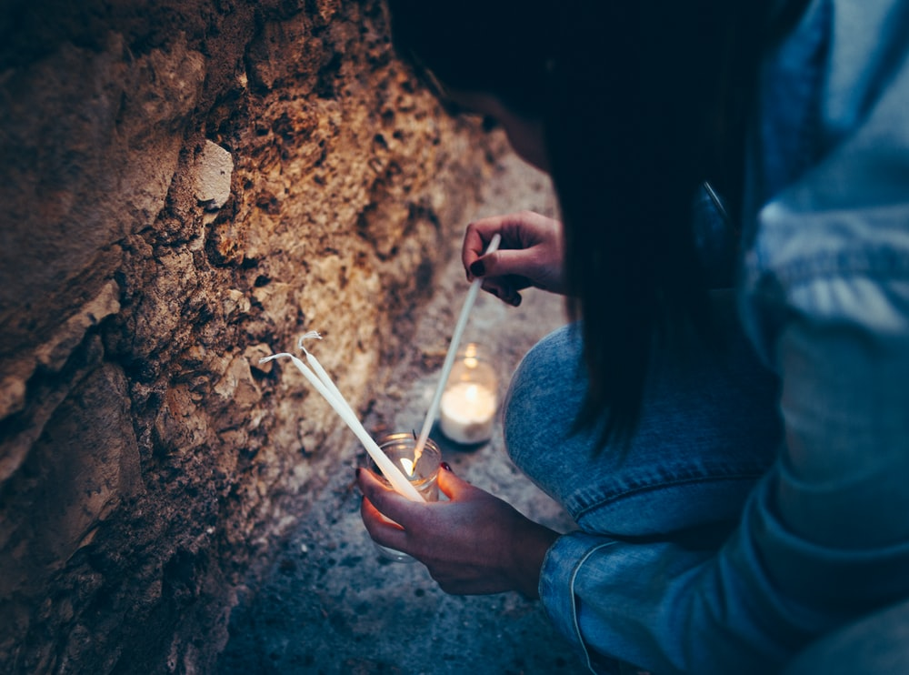woman holding white pillar candles