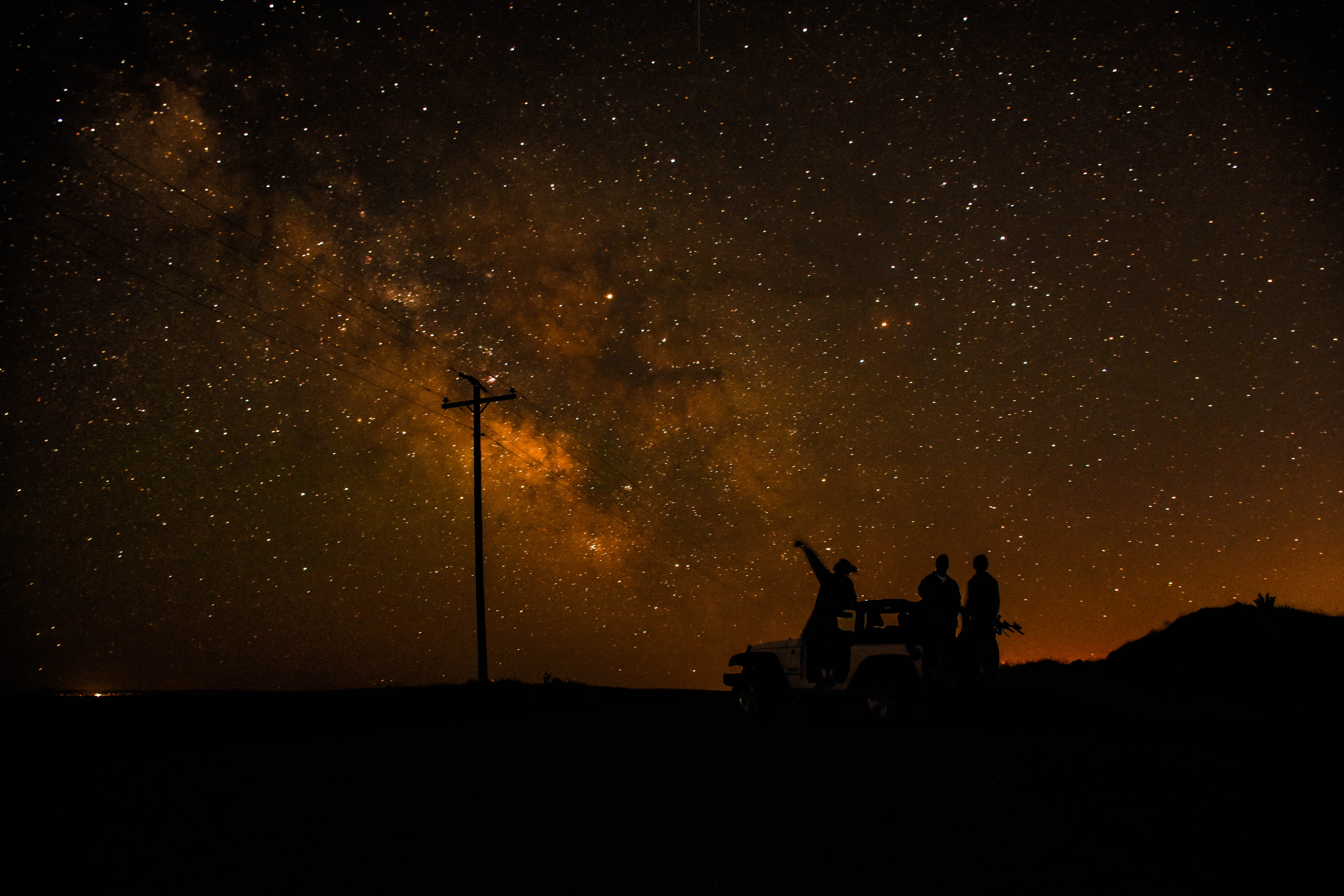 Silhouette of people in Rexburg standing by a jeep looking and pointing at the stars above