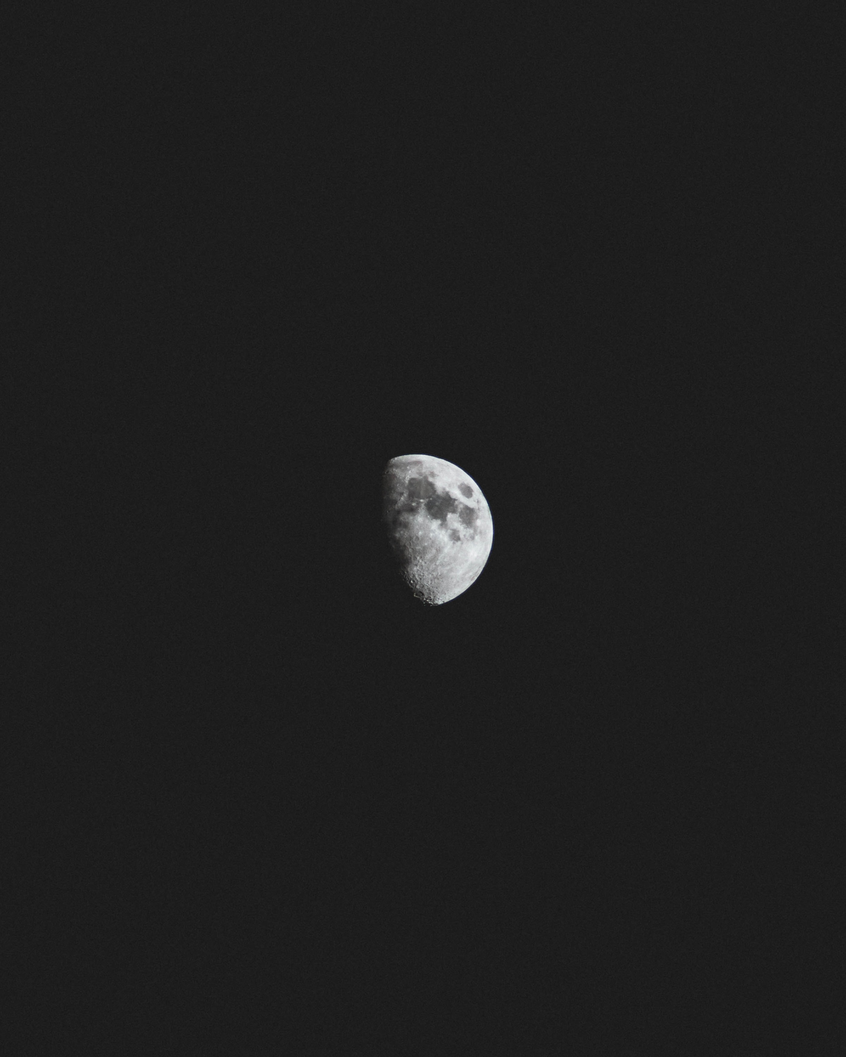 Dark spots visible on a half-moon against a black night sky
