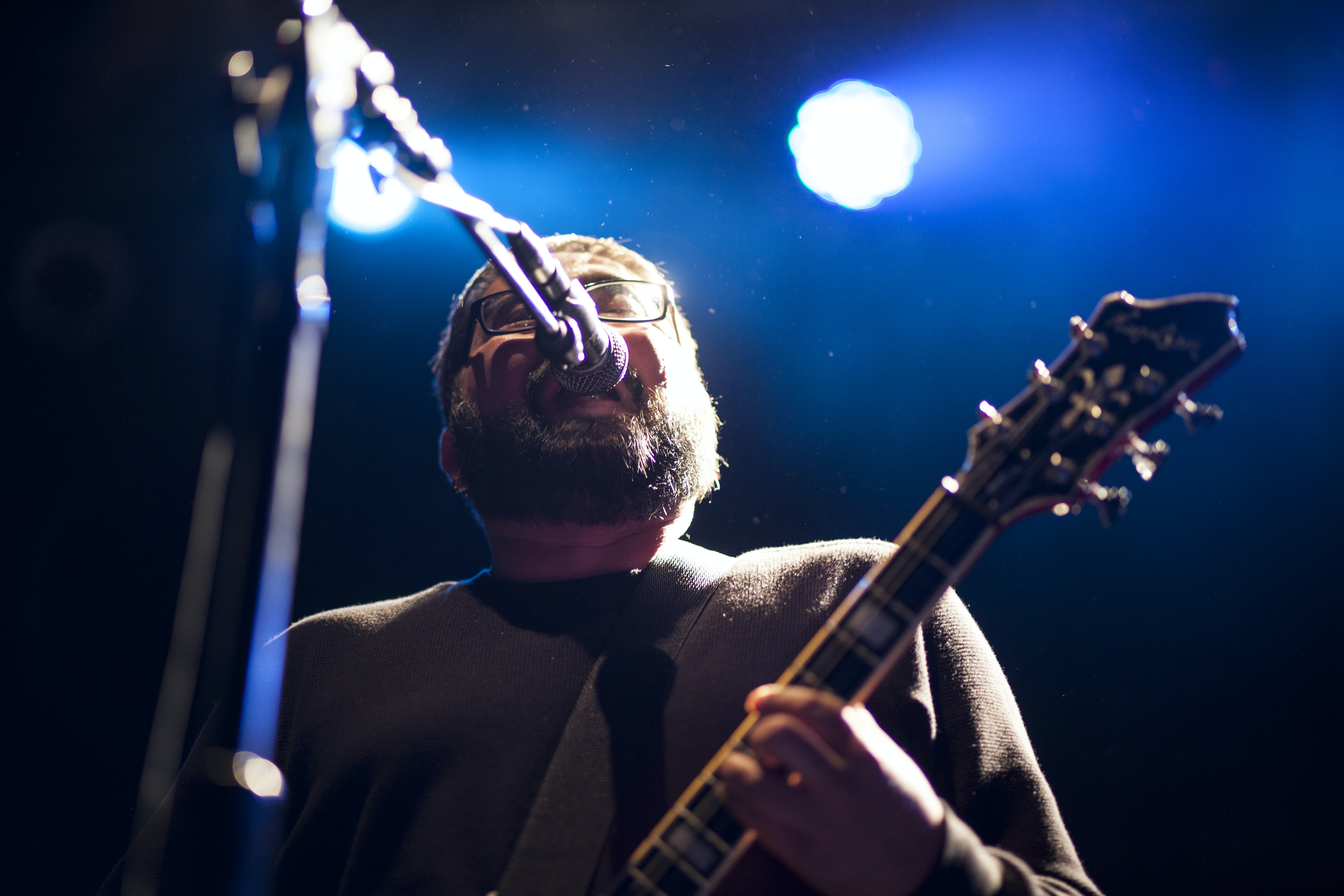 A man with a beard playing the guitar and singing at a concert