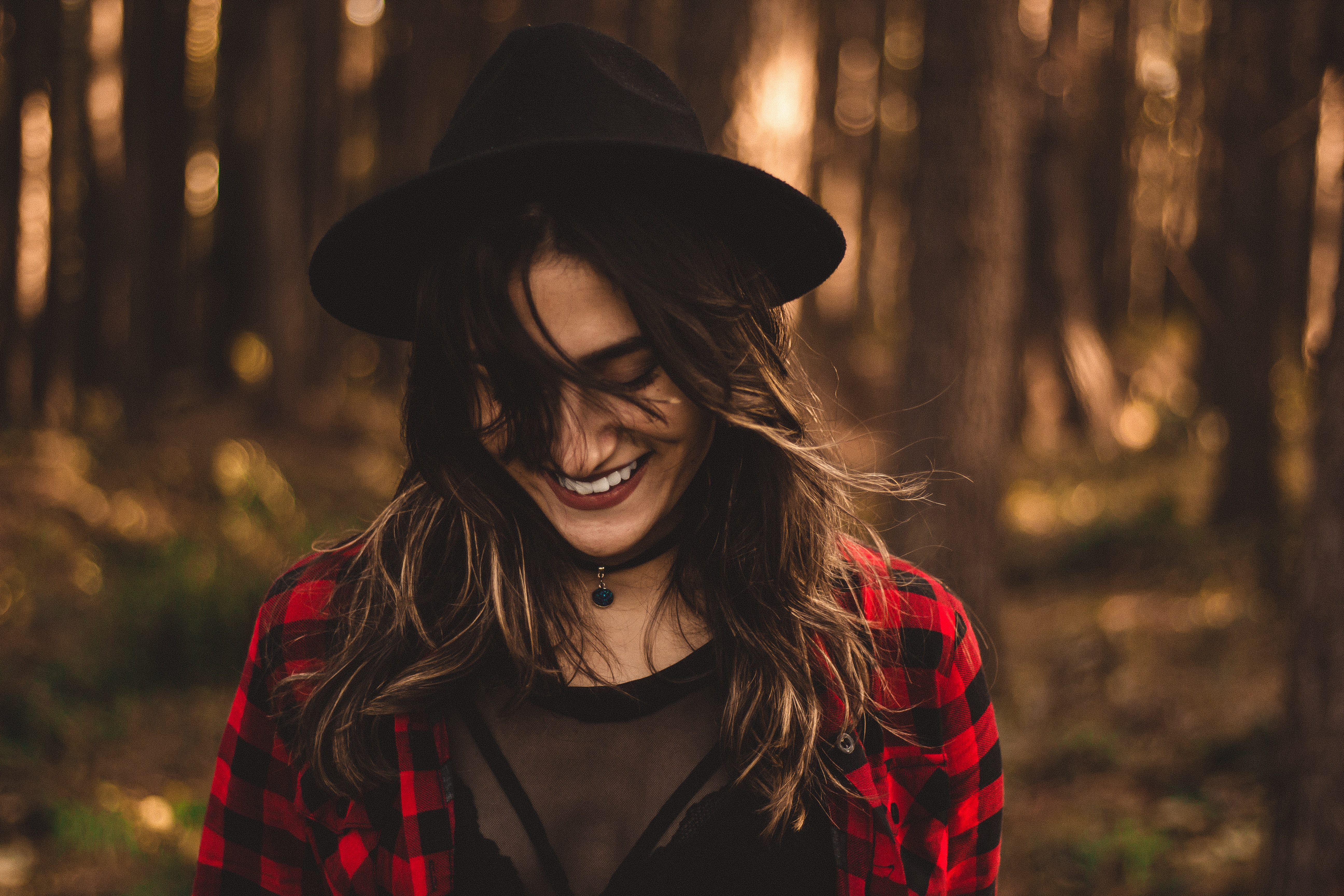 woman in fedora hat surrounded by trees
