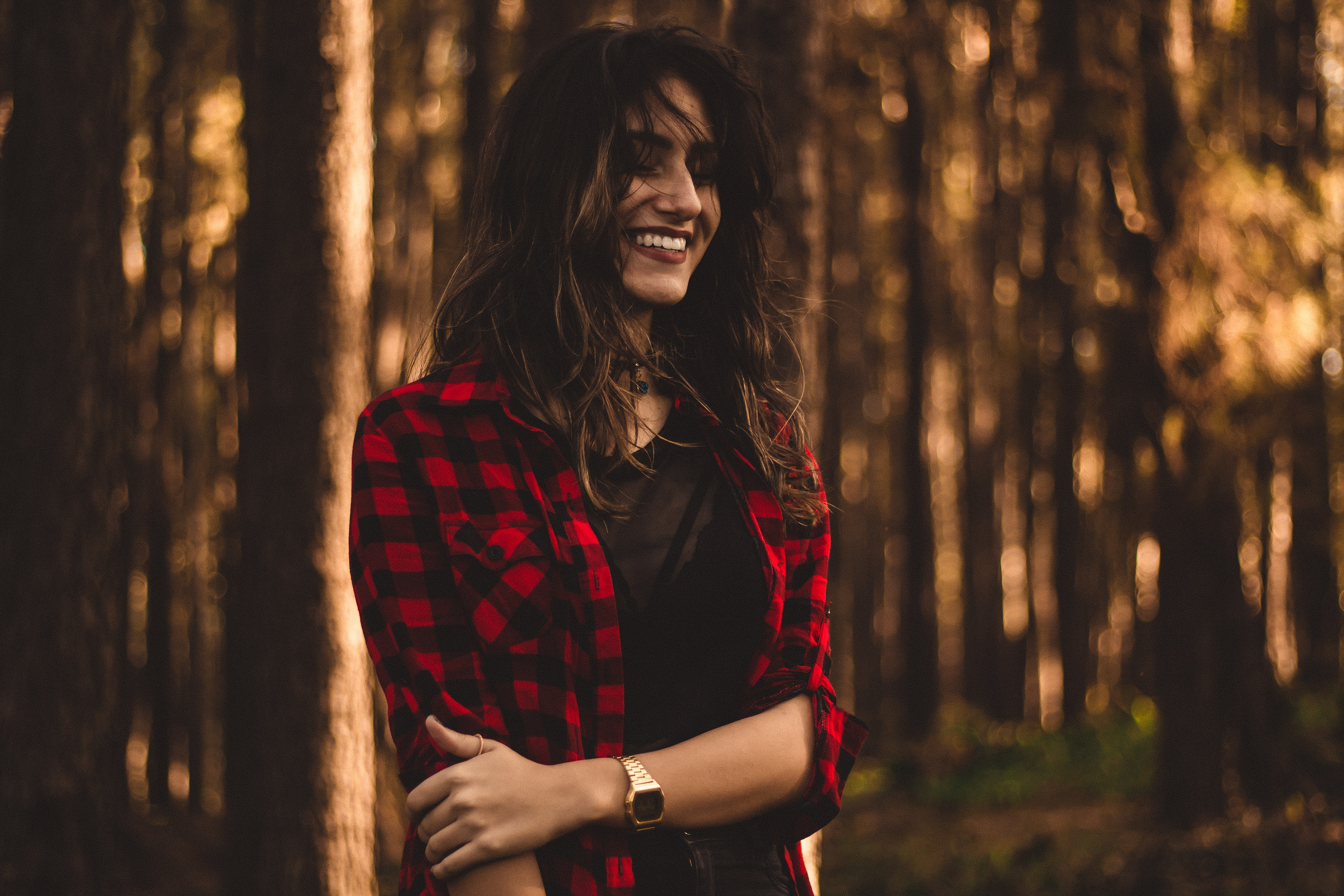 Brown haired woman wearing a plaid, red and black jacket and a watch in the forest