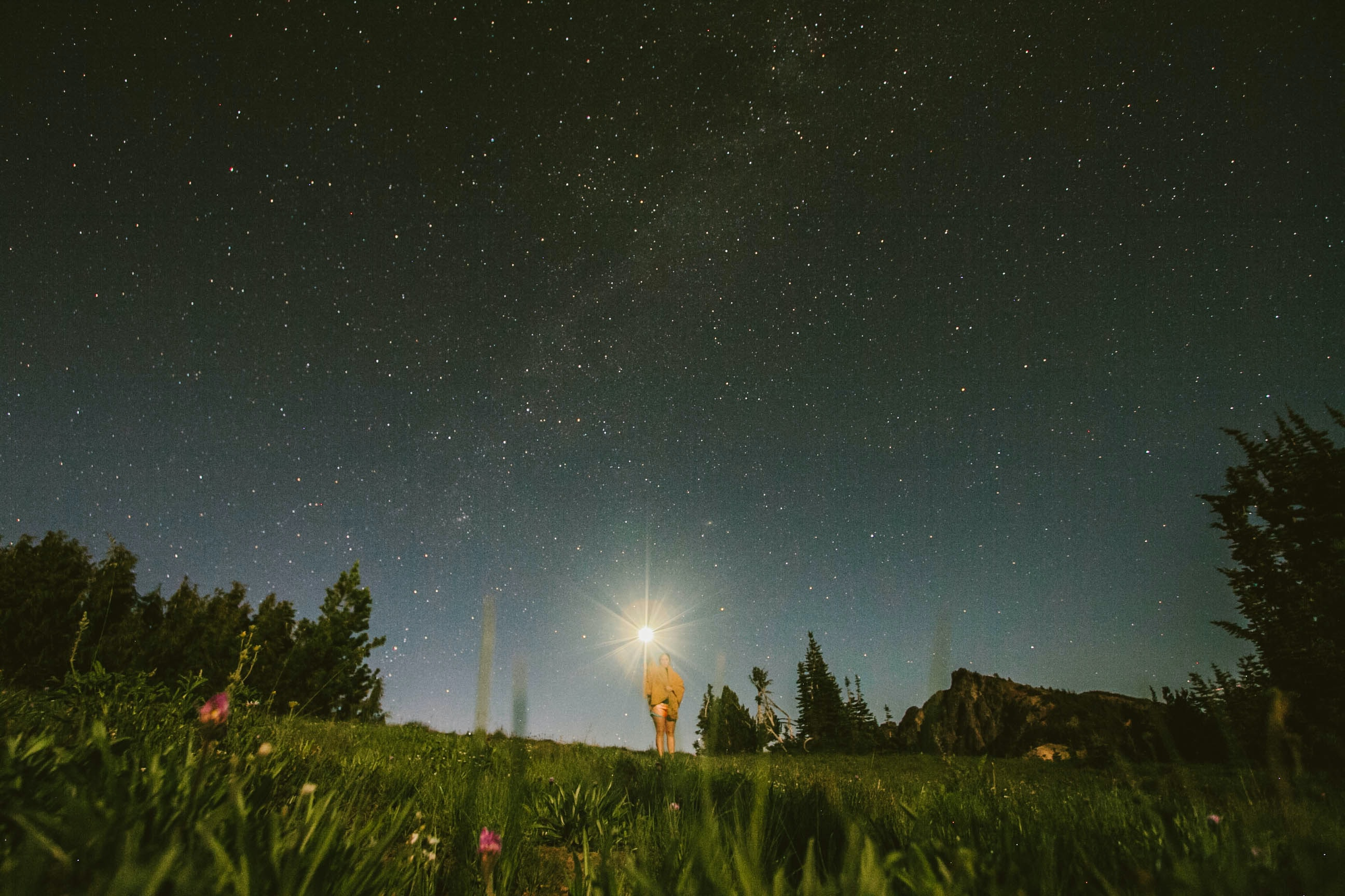 A starry night sky and a woman standing in the grass, wearing a yellow blanket, and holding a flashlight