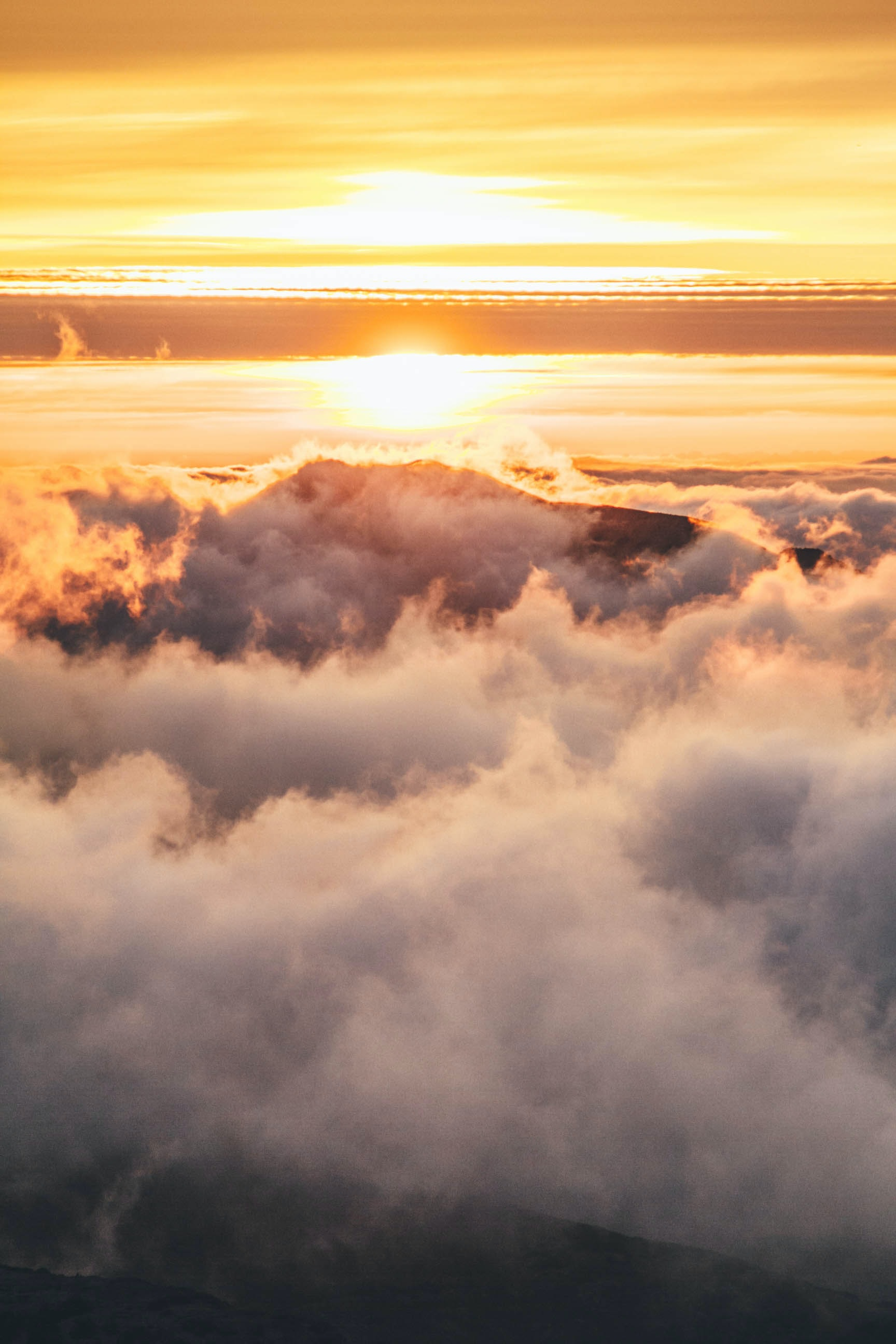 An atmospheric shot of a cloudscape from atop a mountain peak at sunset