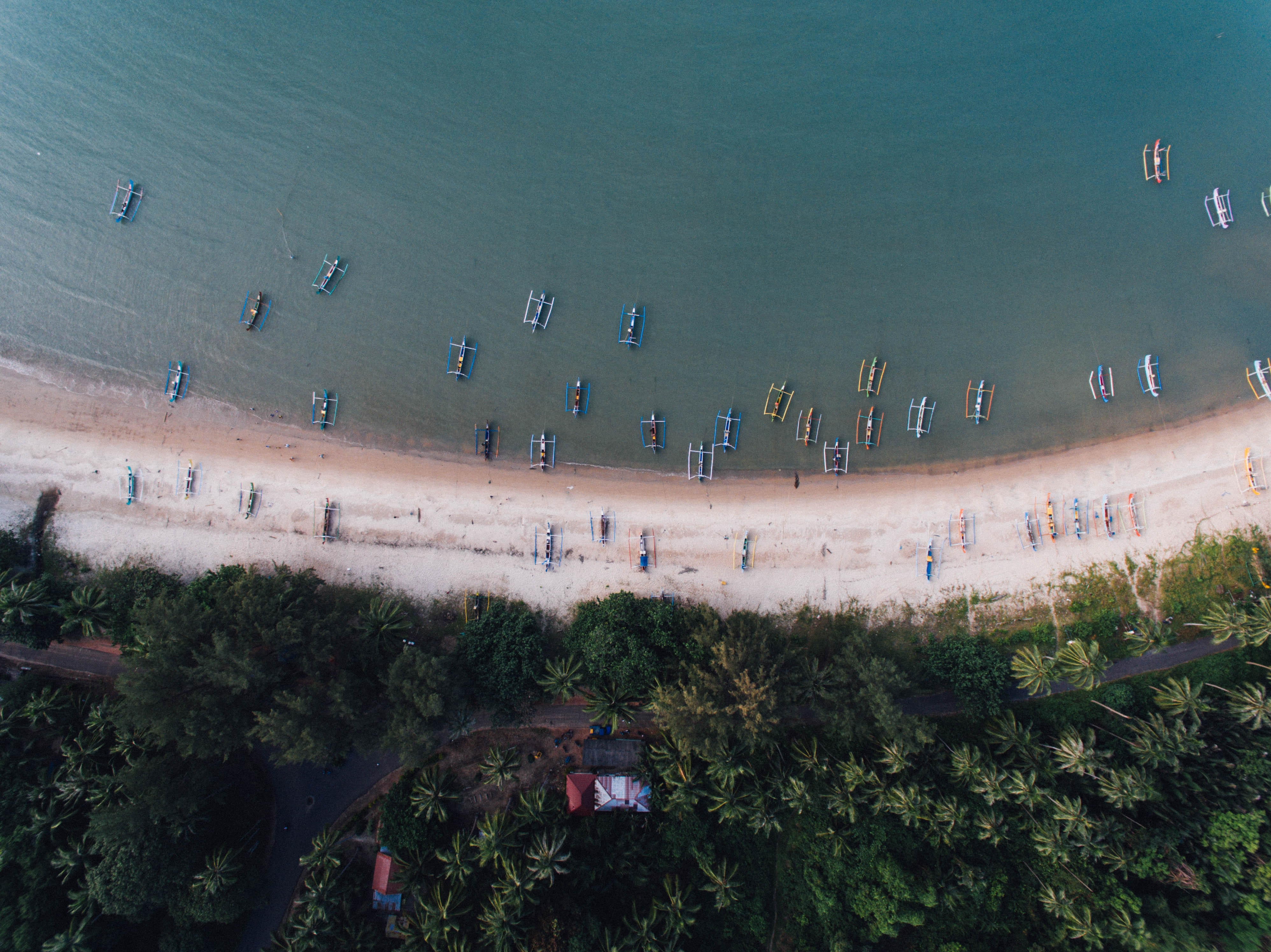 Drone view of traditional fishing catamaran boats in the shallow waters at Belitung