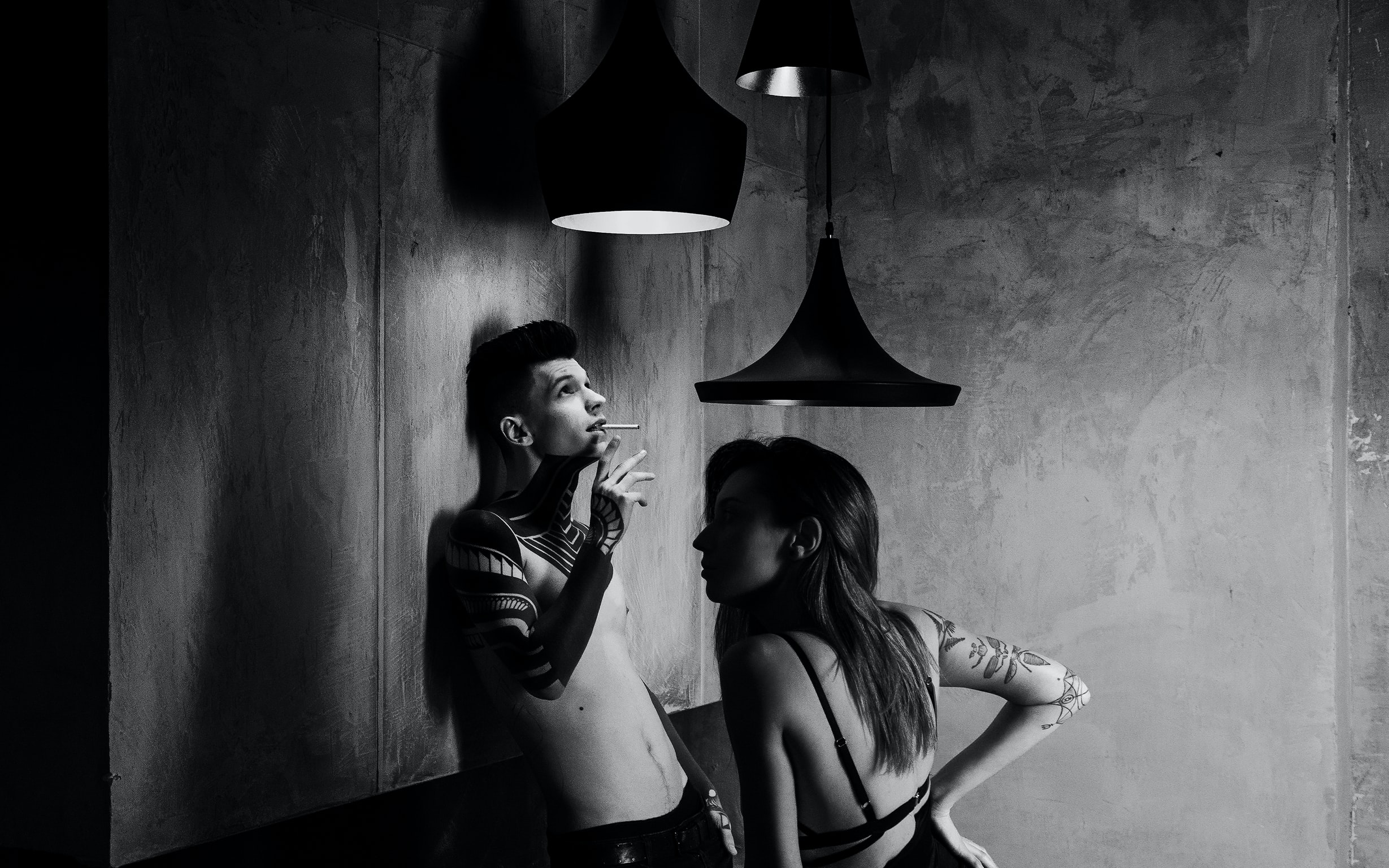 Black and white shot of topless man with tattoos smoking with woman under ceiling lamps