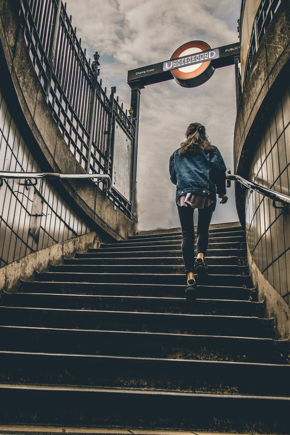 woman in blue denim button-up jacket walking on concrete stairs during daytime