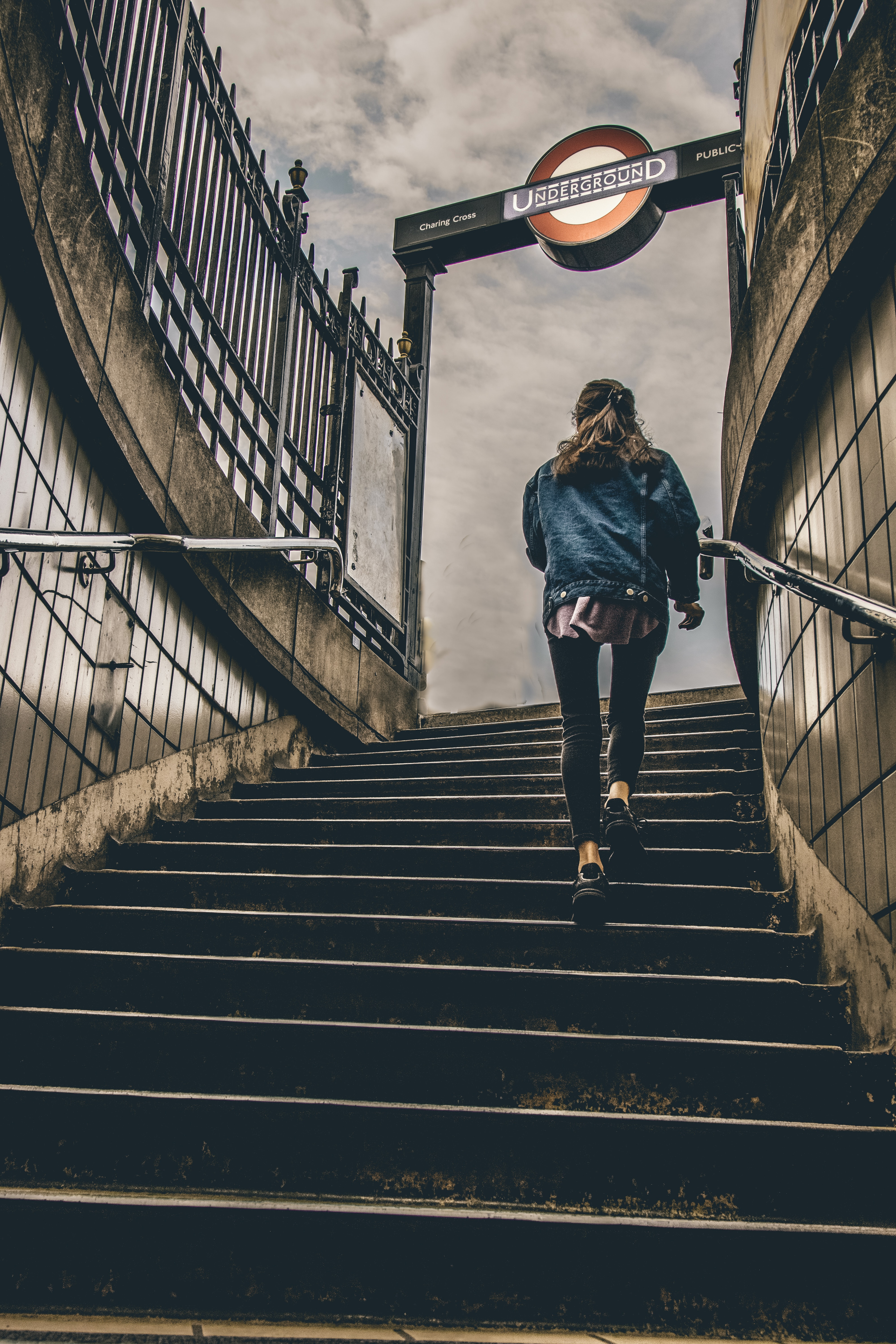A woman climbing up the stairs at a London Underground station
