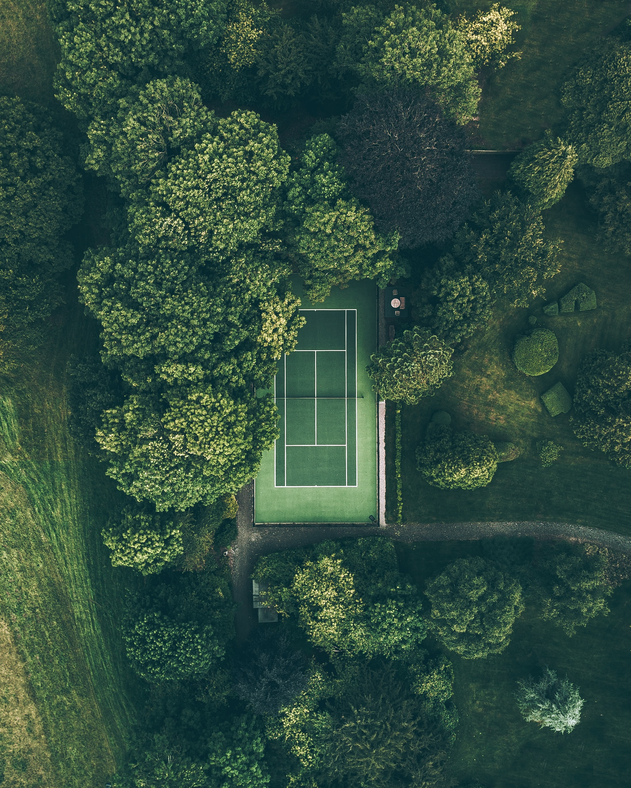 A drone shot of a green tennis court surrounded by trees in Frampton, England
