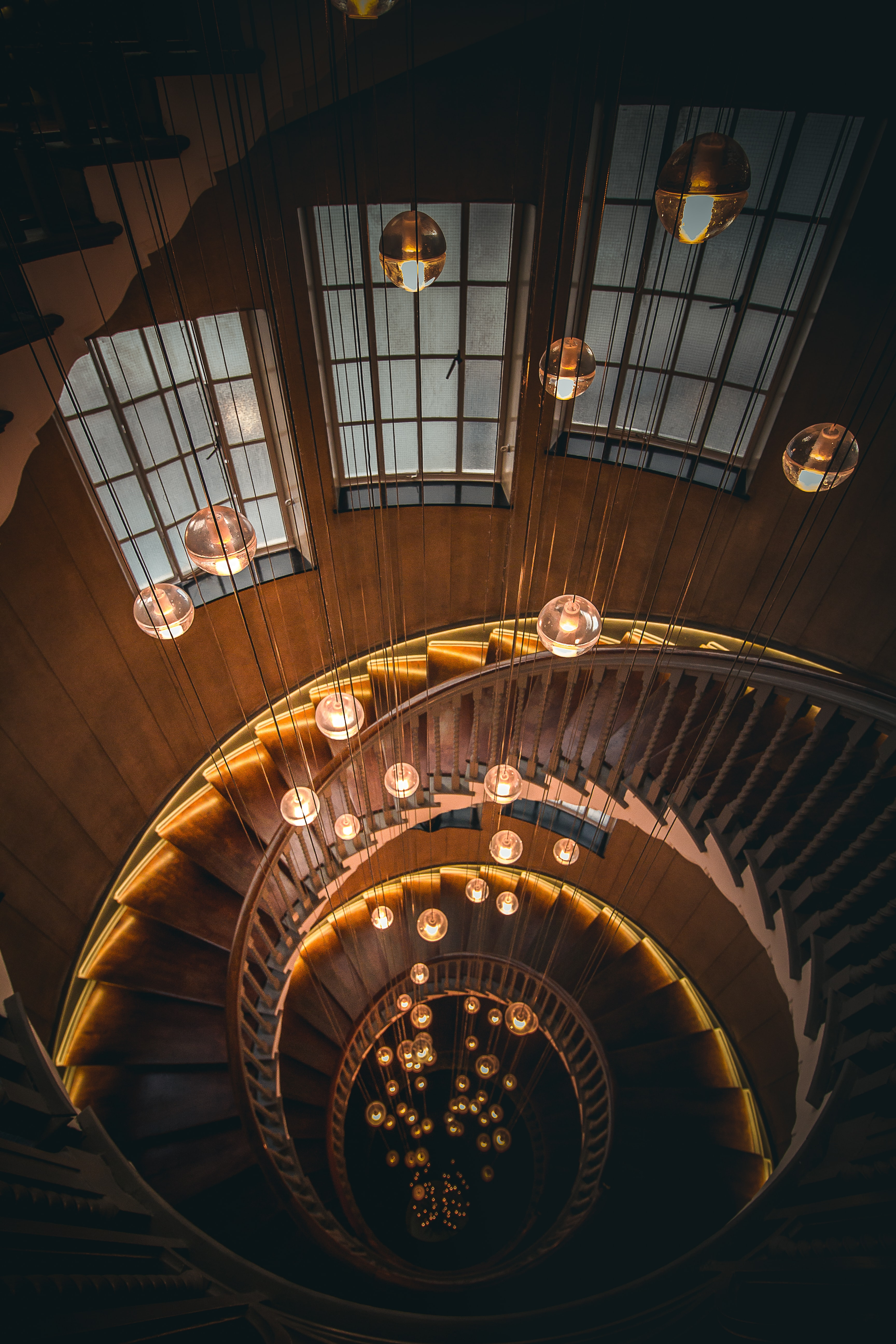 Looking down on a spiral staircase with hanging lightbulbs at Heal's