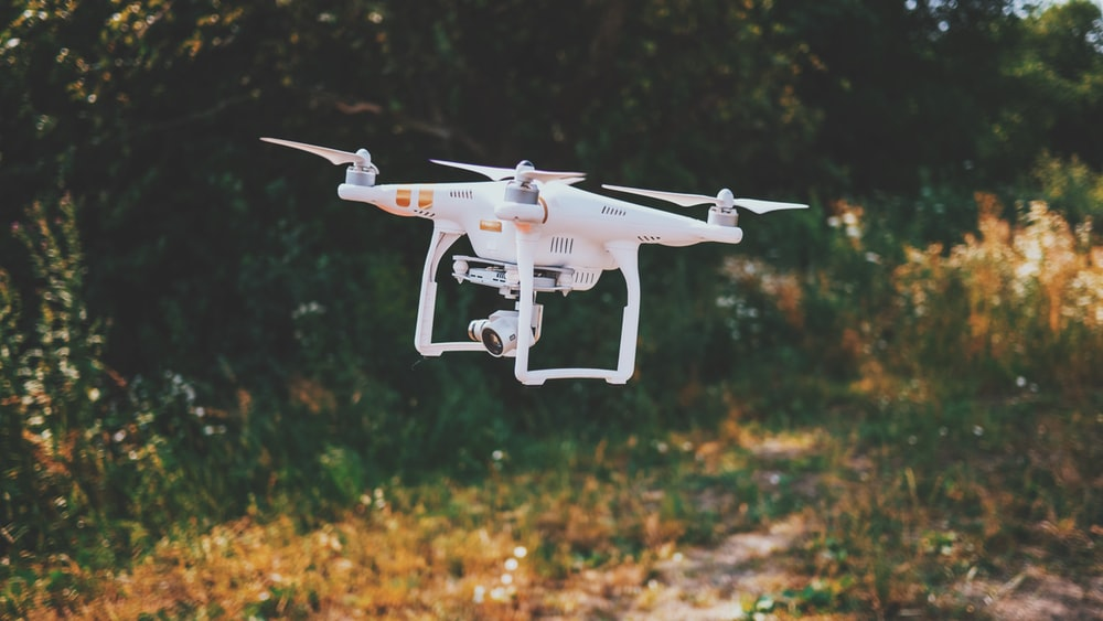 white drone flying outdoor during daytime