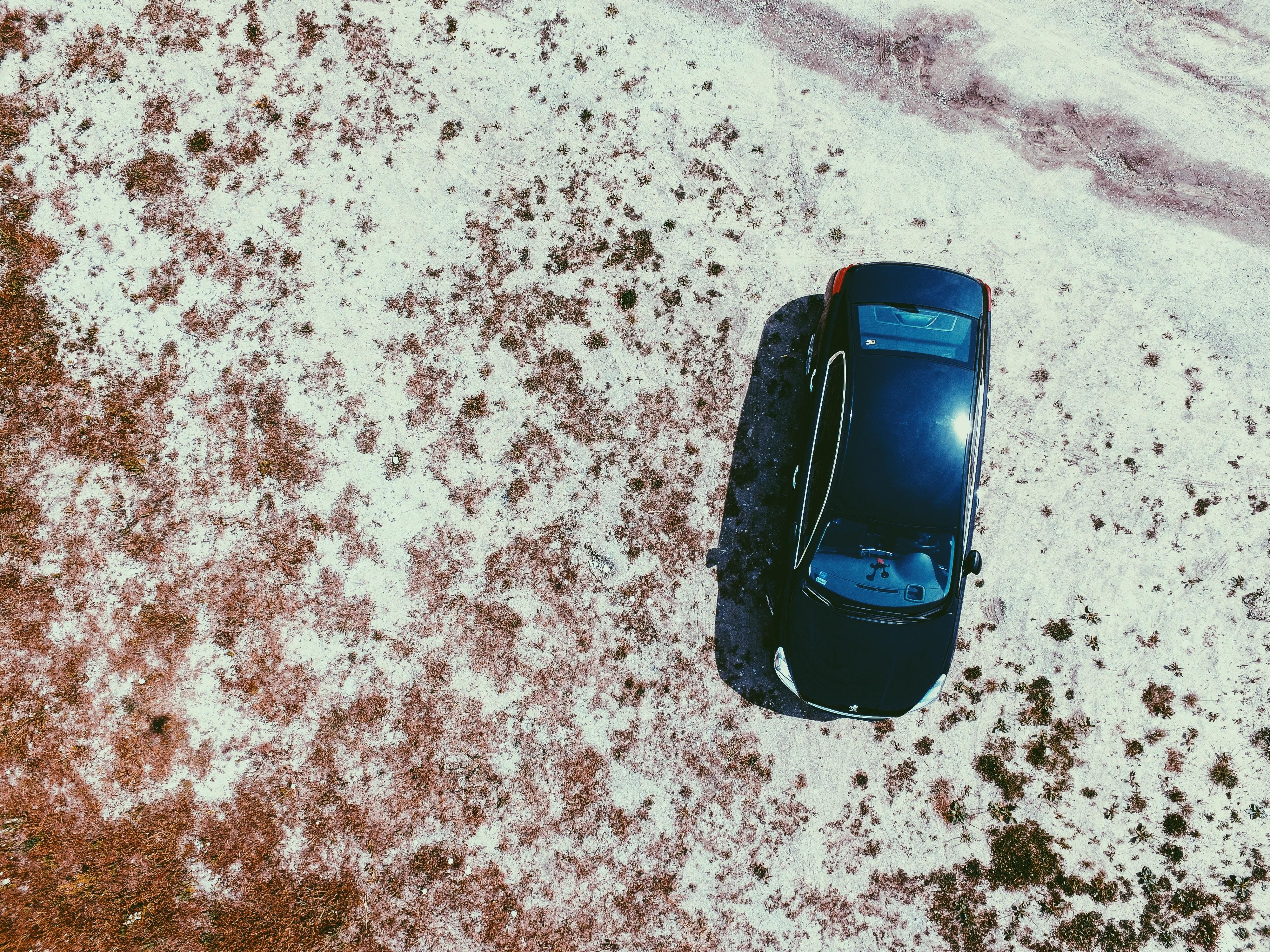 Drone shot of a black sedan automobile in the desert landscape.