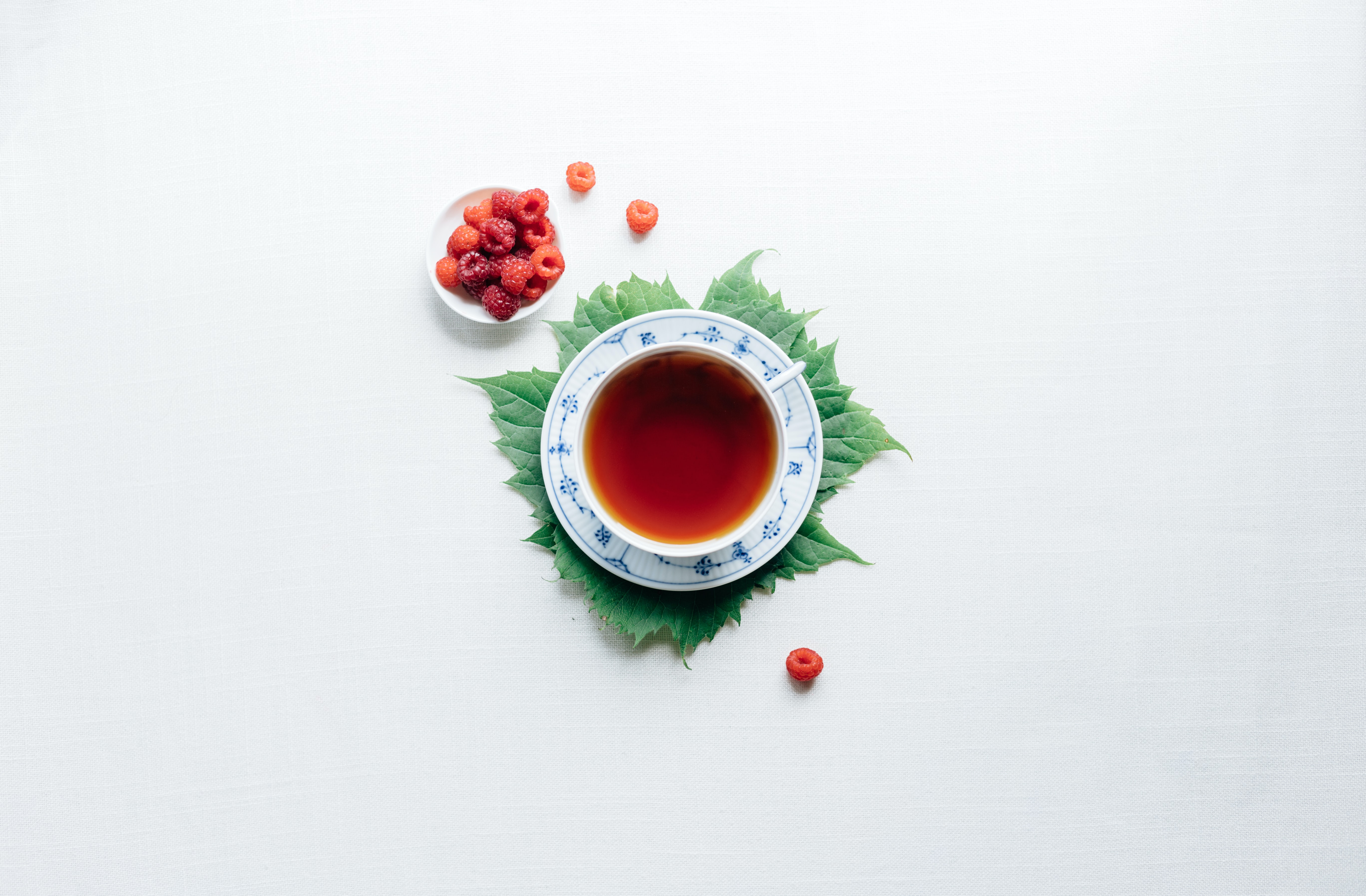 round white cup with saucer filled with red liquid