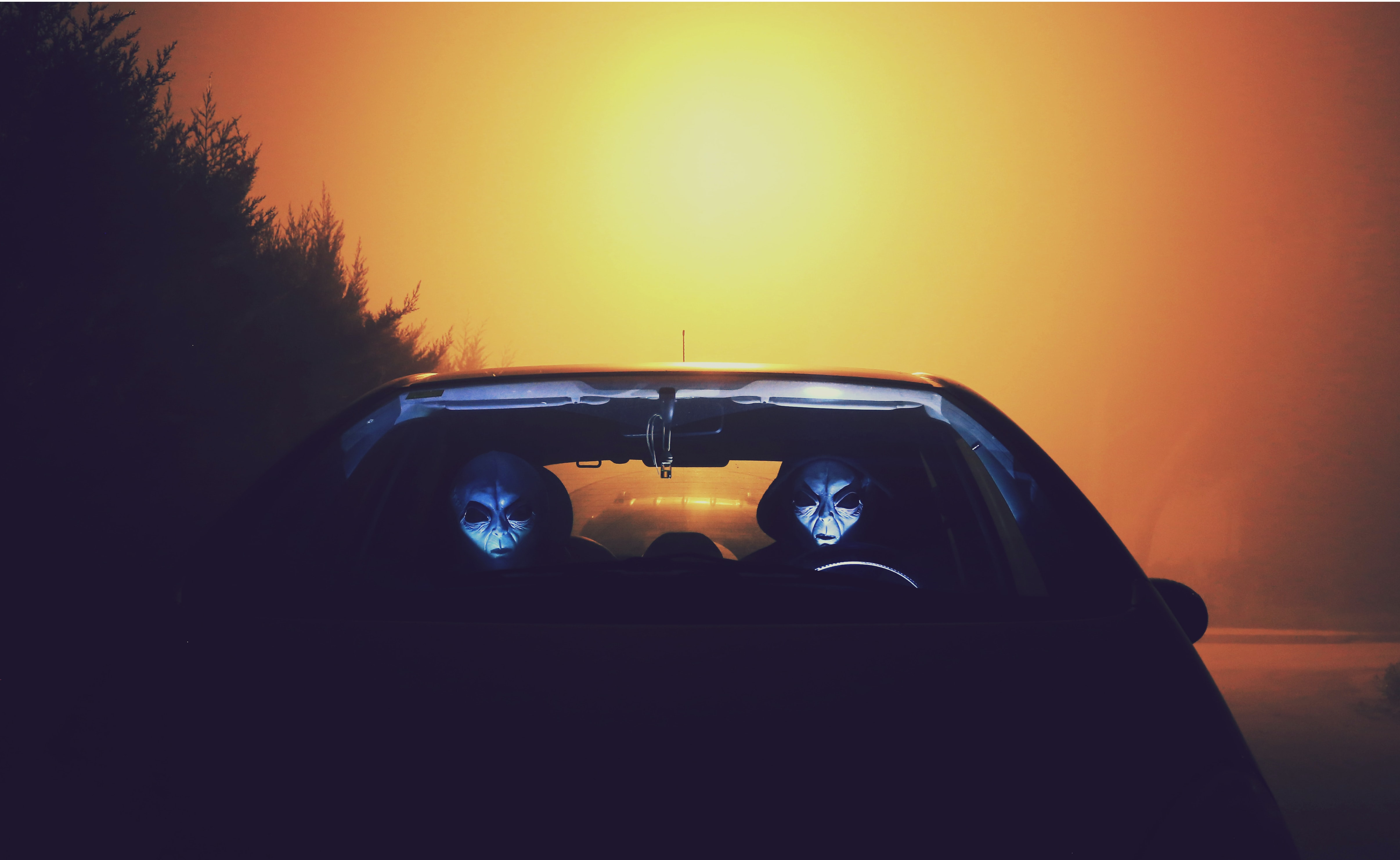 Two aliens in the car driving away from the Sun in Catalonia