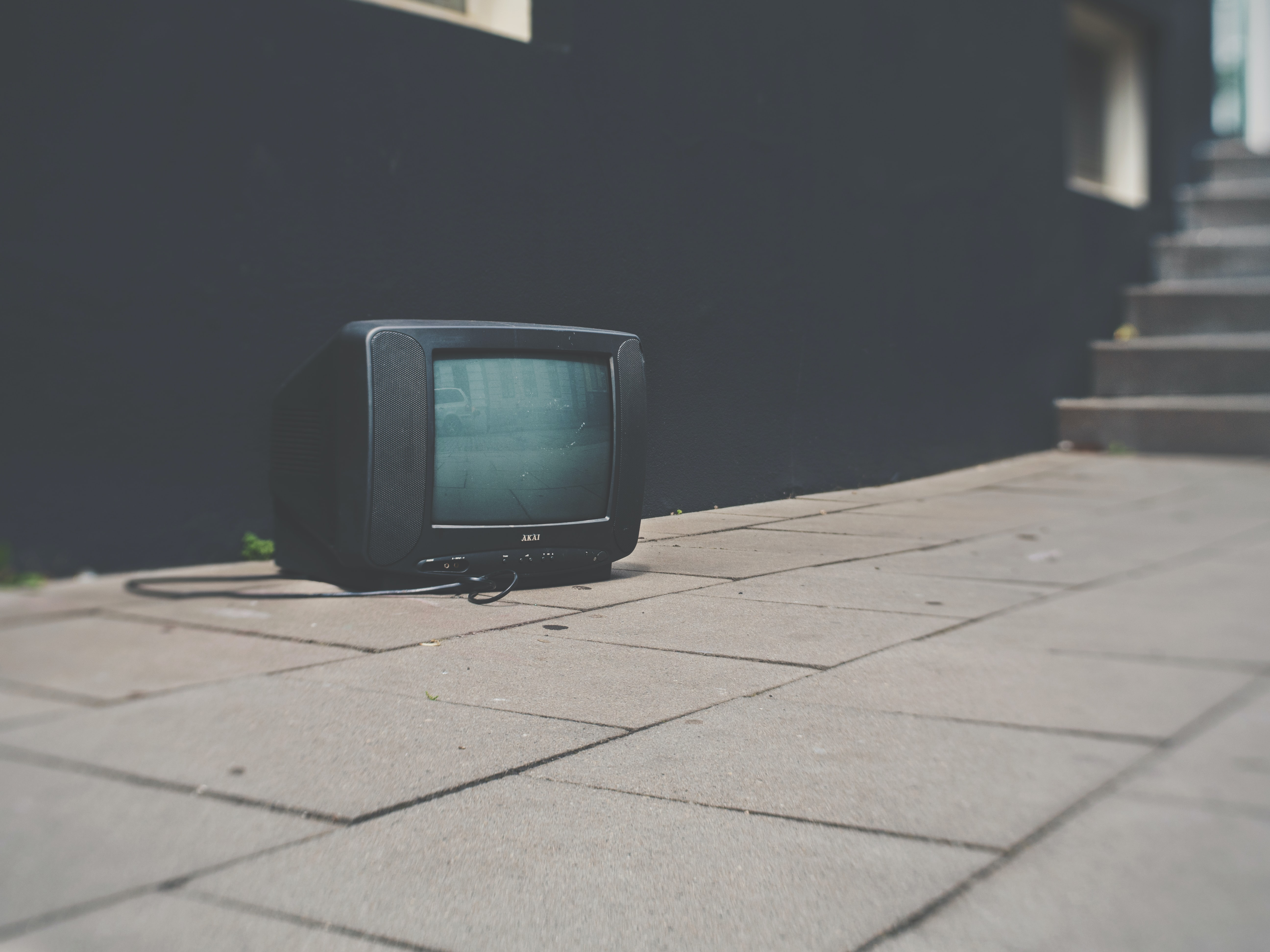 Television with cord sitting on sidewalk outside of black building near stairs